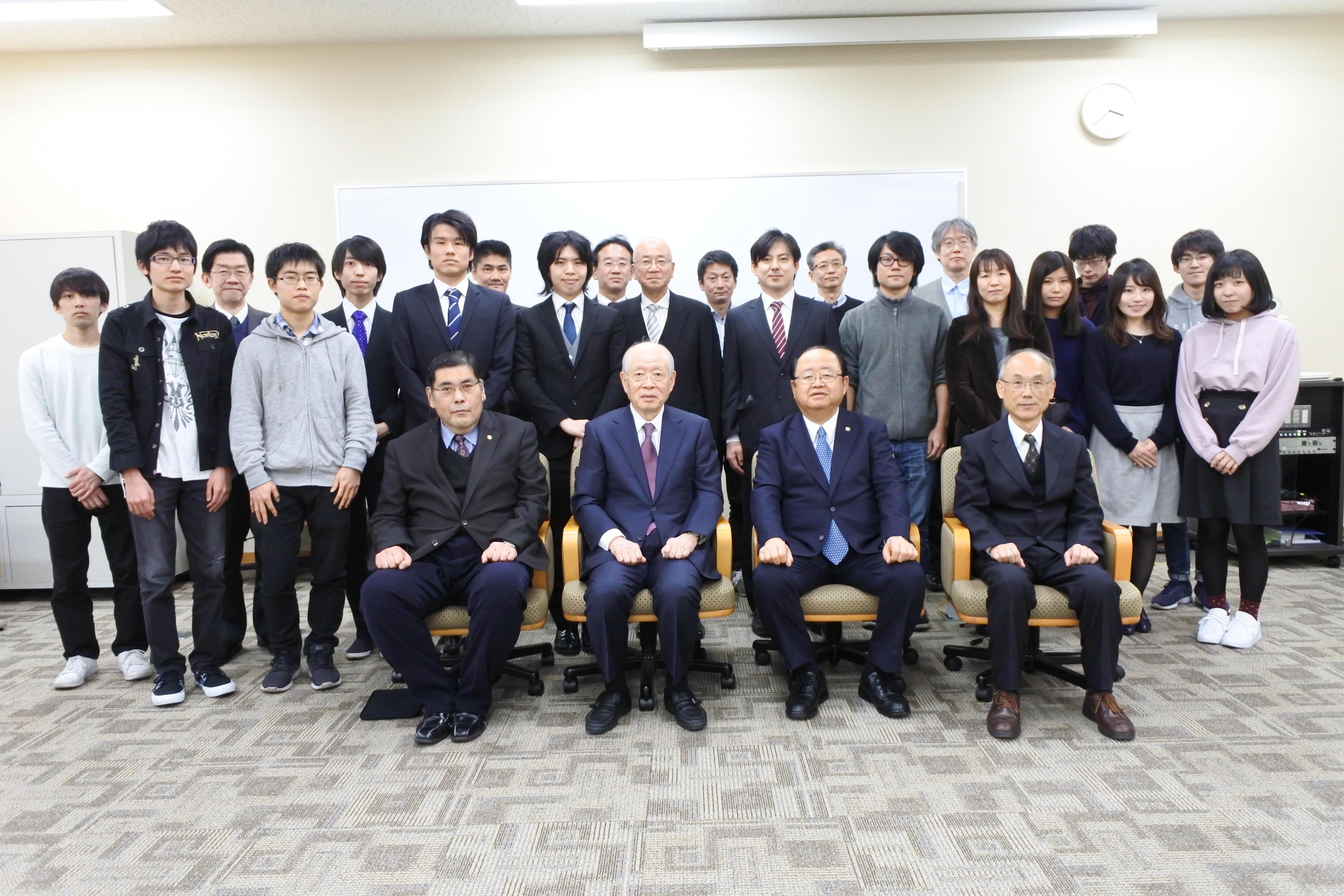 野依客員教授(前列左から2人目)と一緒に写真に納まる立花貞司理事長(同3人目)ら参加者