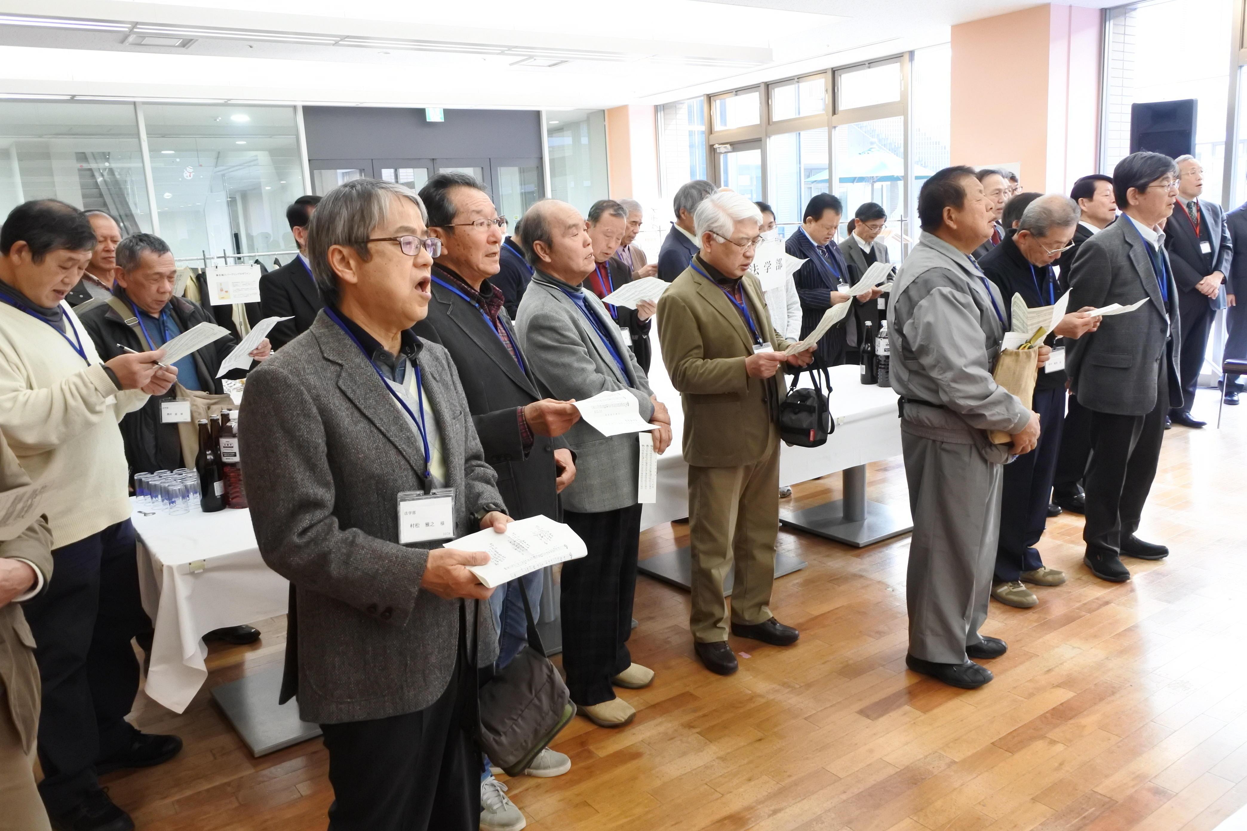 学歌を斉唱する参加者