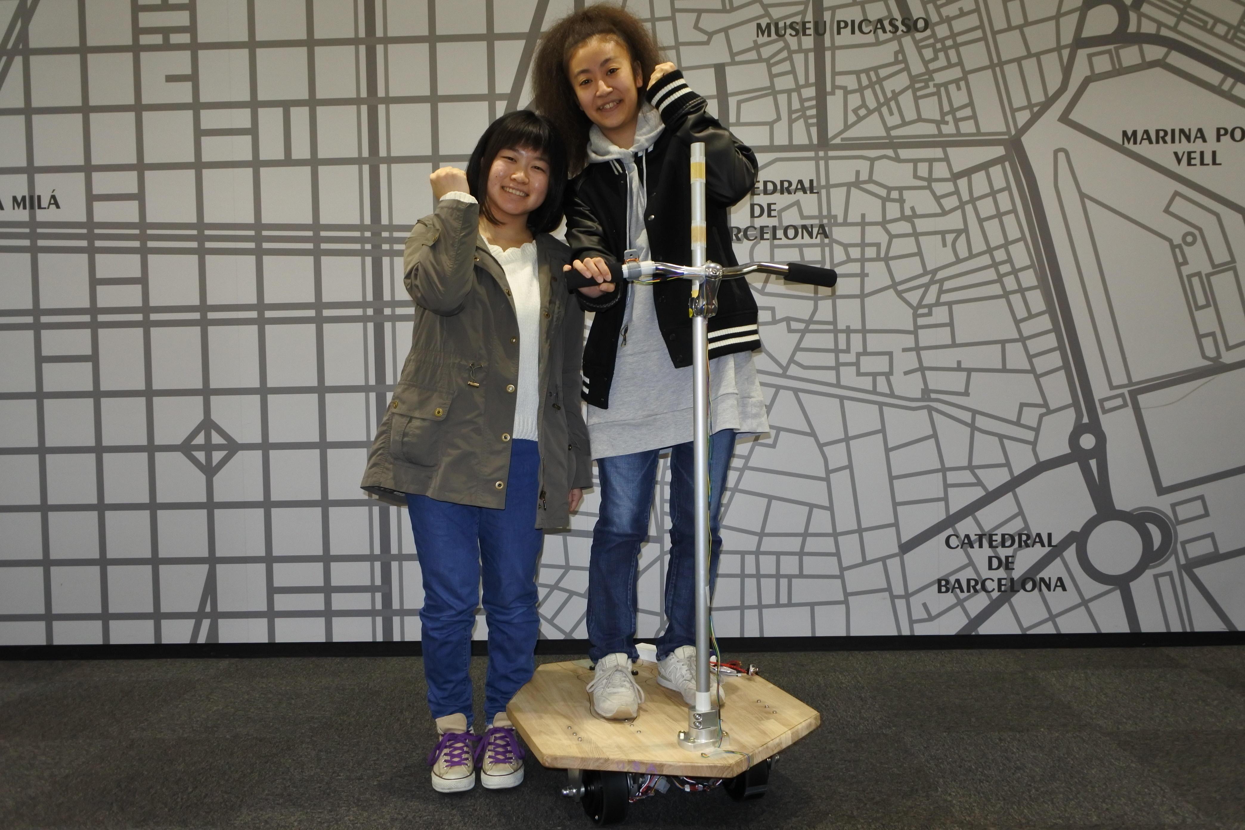 自作の電動立ち乗り三輪車に乗る鈴木さん(右)と、井上さん
