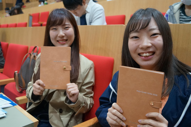 募金を活用した就職手帳を手にする学生たち