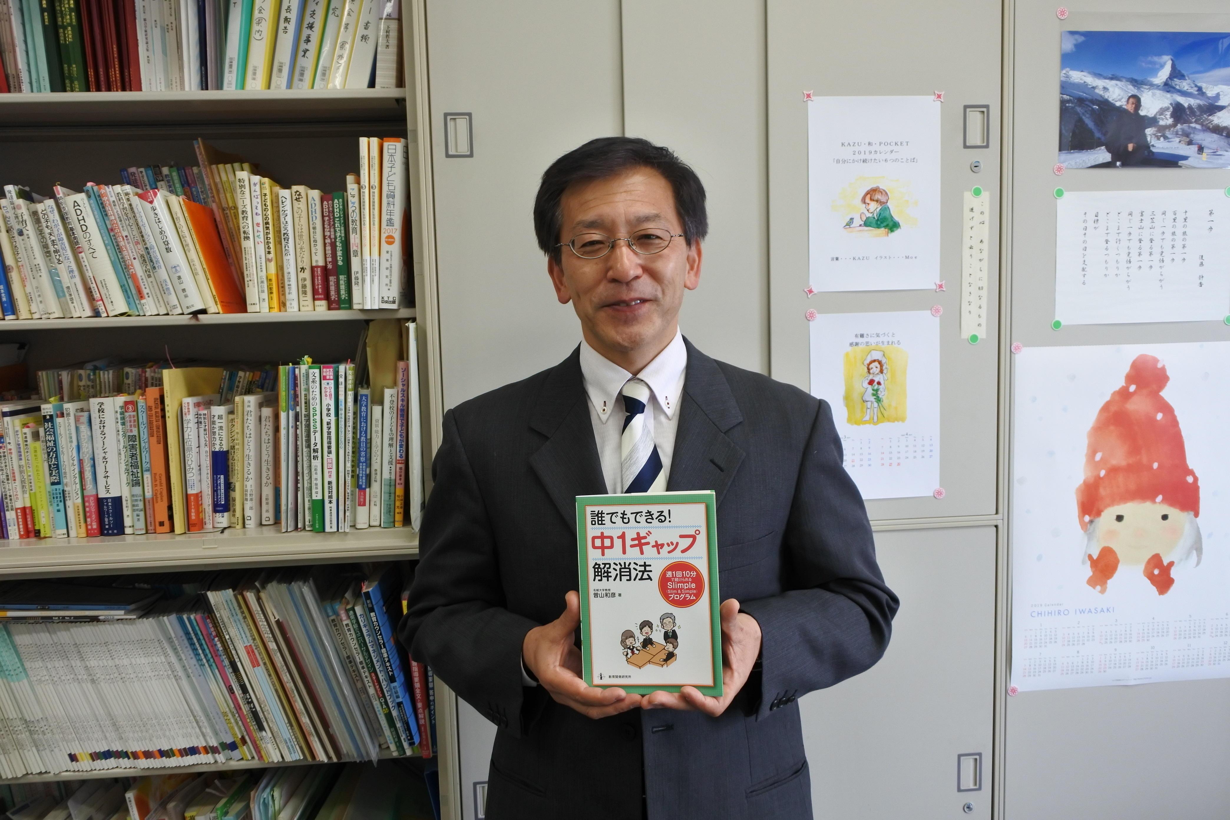 著書を手にする曽山教授