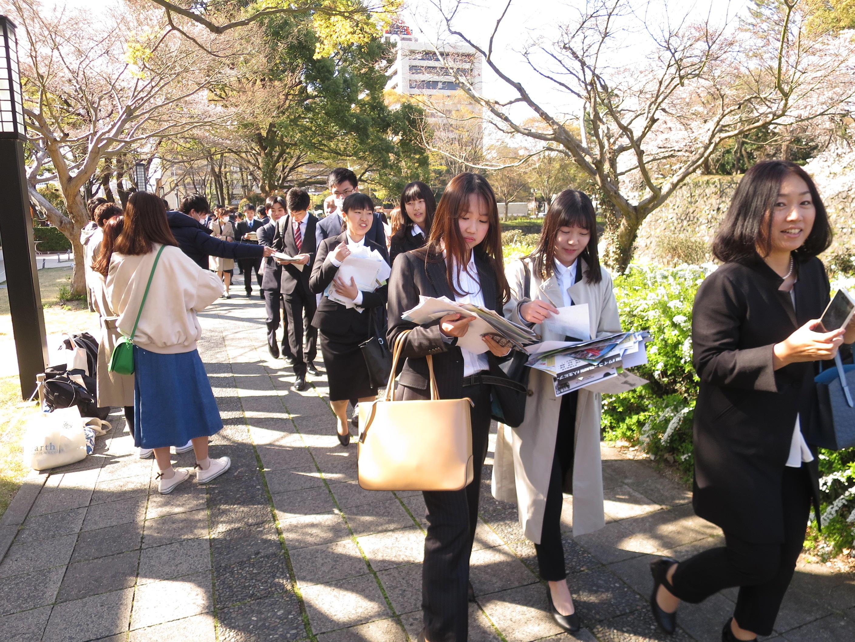 サークル勧誘のチラシをもらいながら入学式場に向かう新入生たち