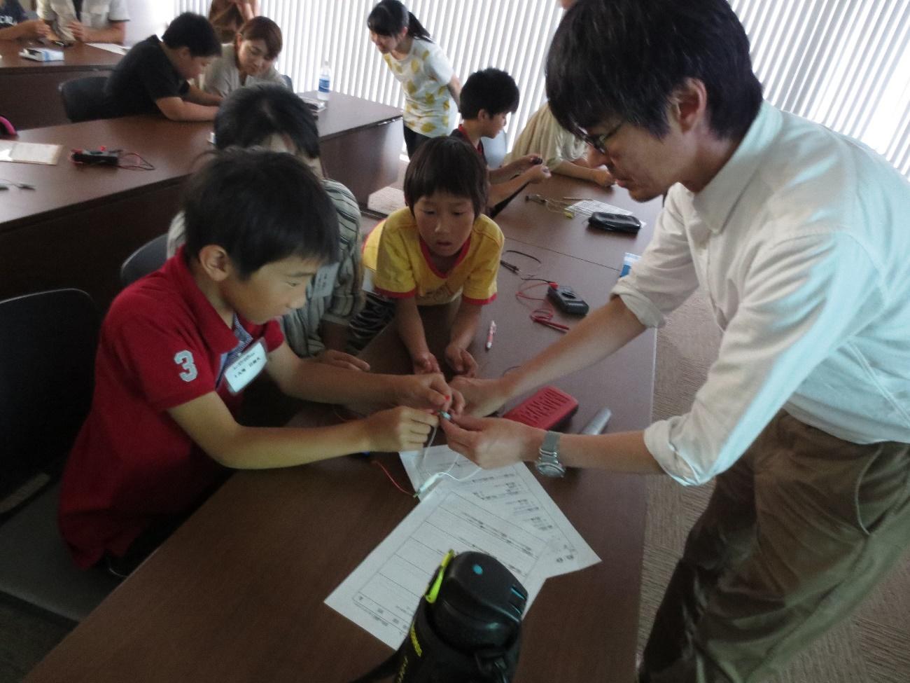 青色LEDを光らせる児童と竹内教授(右)