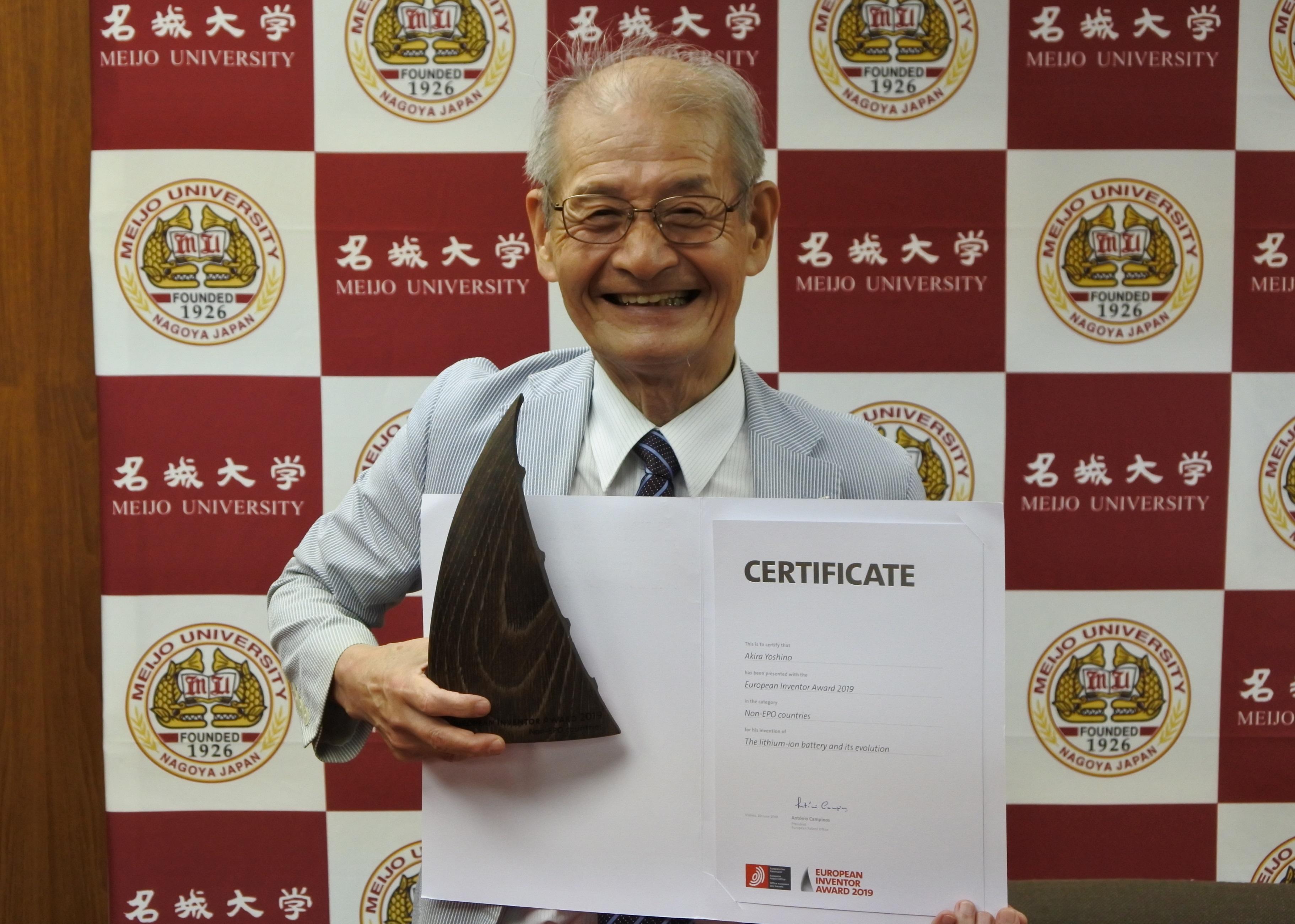 トロフィーと賞状を手に笑顔の吉野彰教授