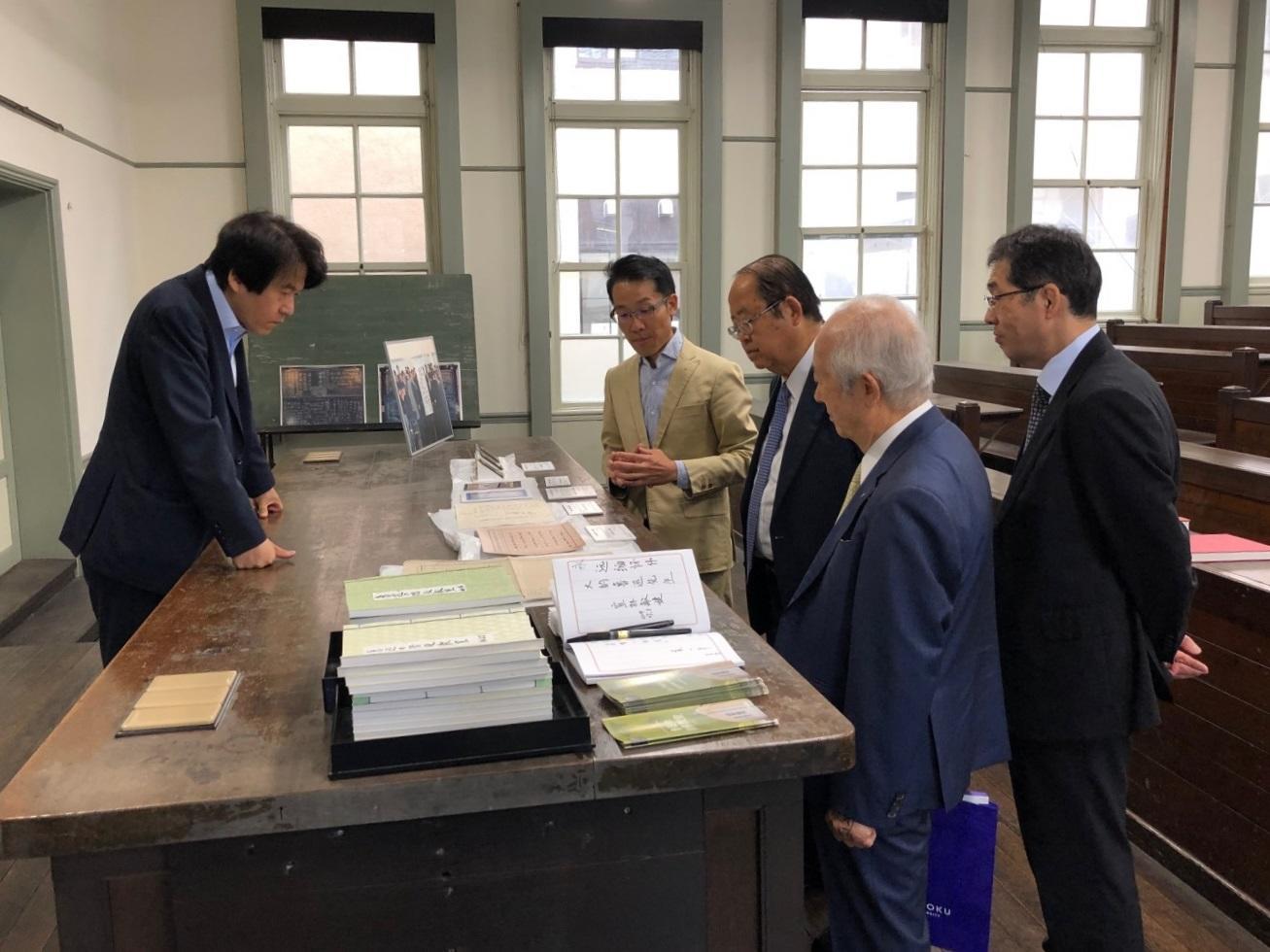 「魯迅の階段教室」で魯迅ゆかりの品々を見る理事長(右から3人目)ら