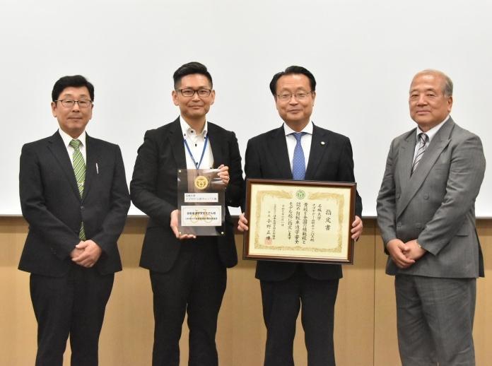指定書、盾を手にする大脇副経営本部長(右から2人目)とナゴヤドーム前キャンパス事務室濱松暢生さん(同3人目)。
