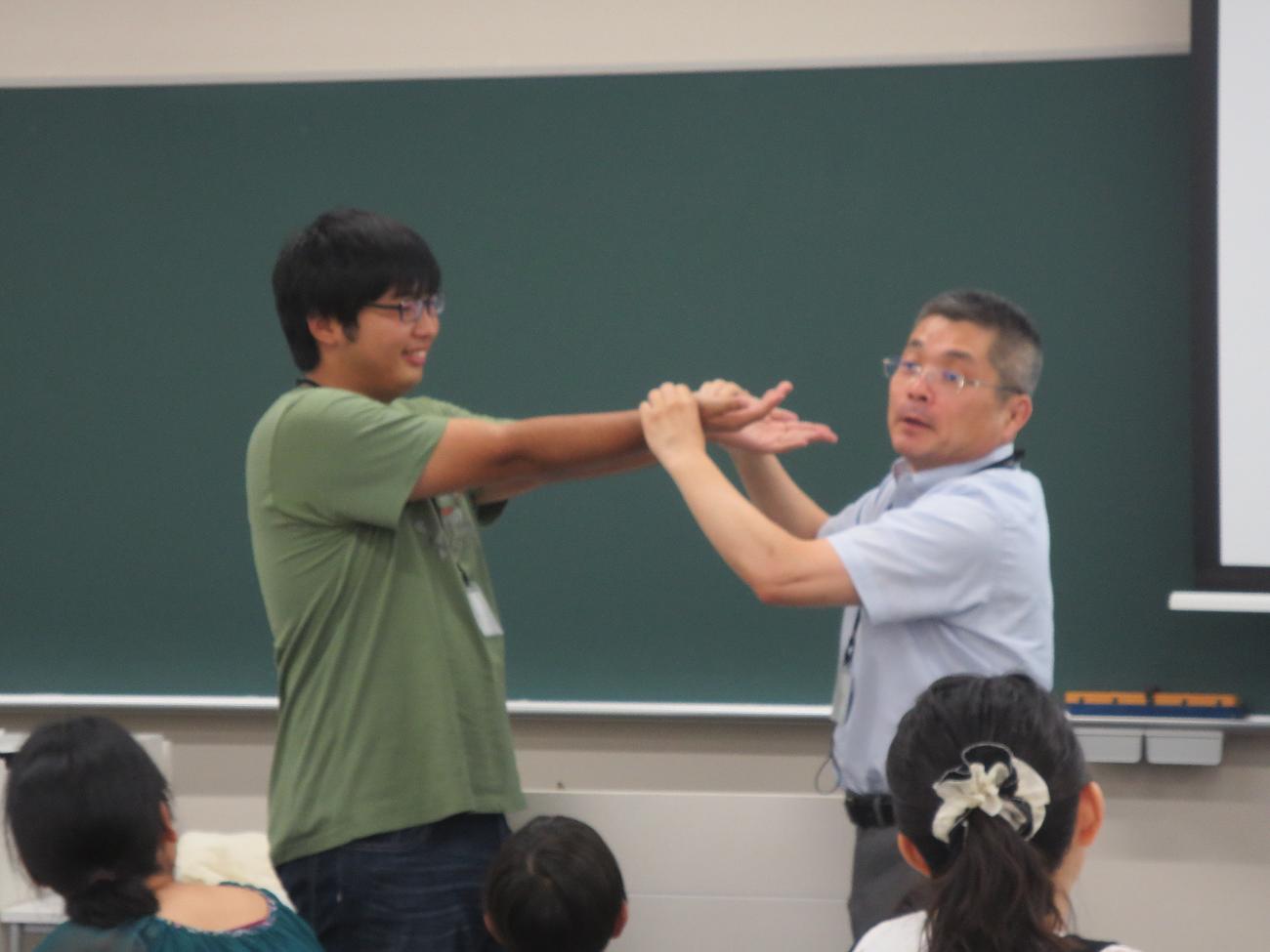 脈の測り方を実践する黒野教授(右)