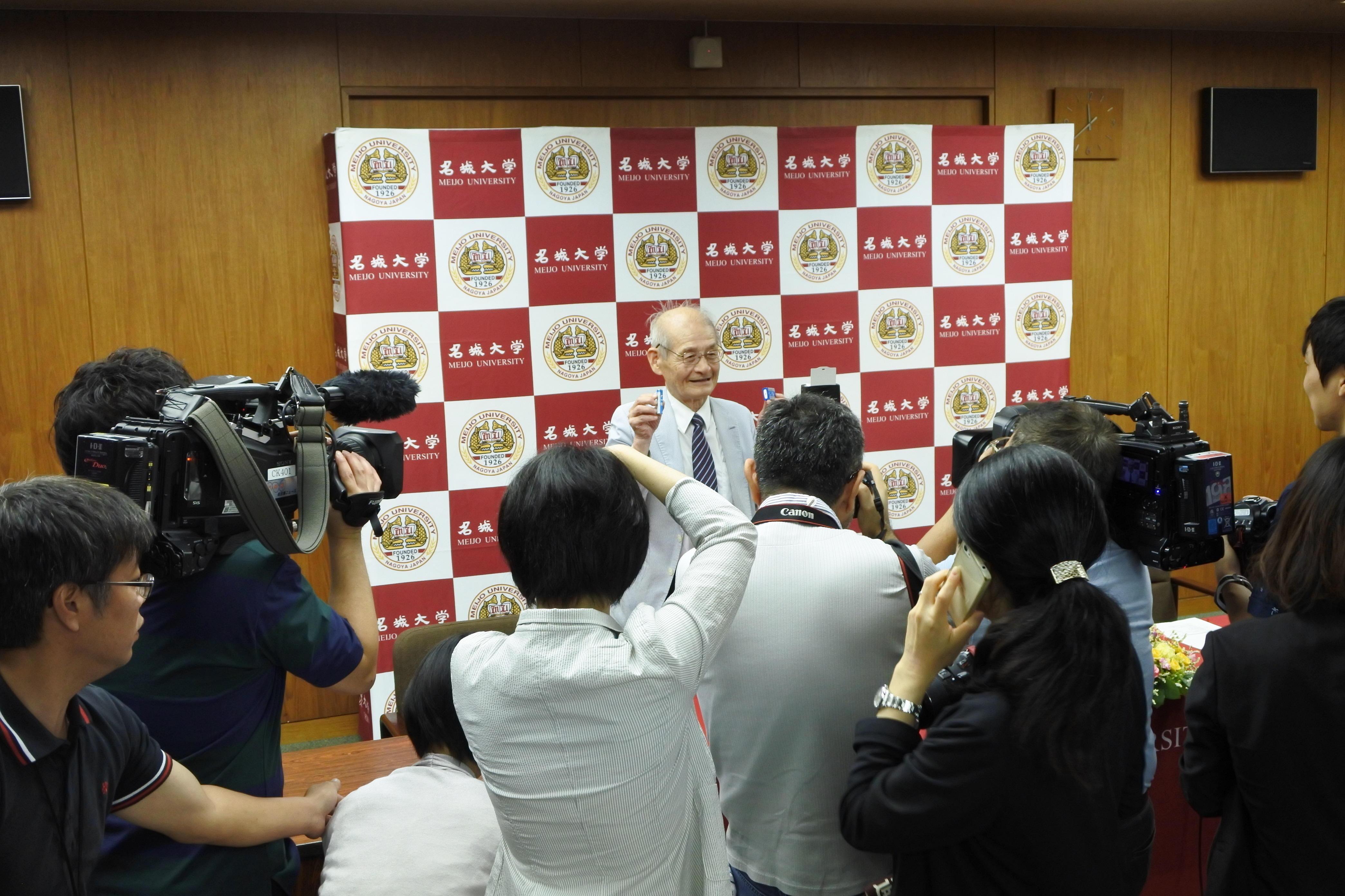 カメラの放列の前で写真撮影に応じる吉野彰教授