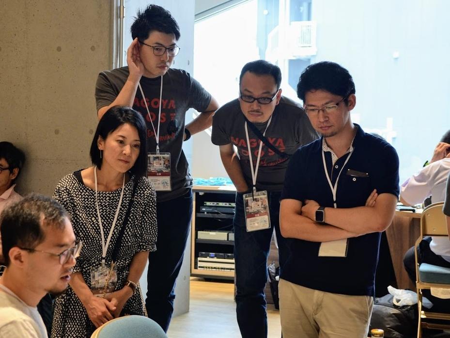 (右)参加者の説明を聞く鈴木准教授(JellyWare撮影)
