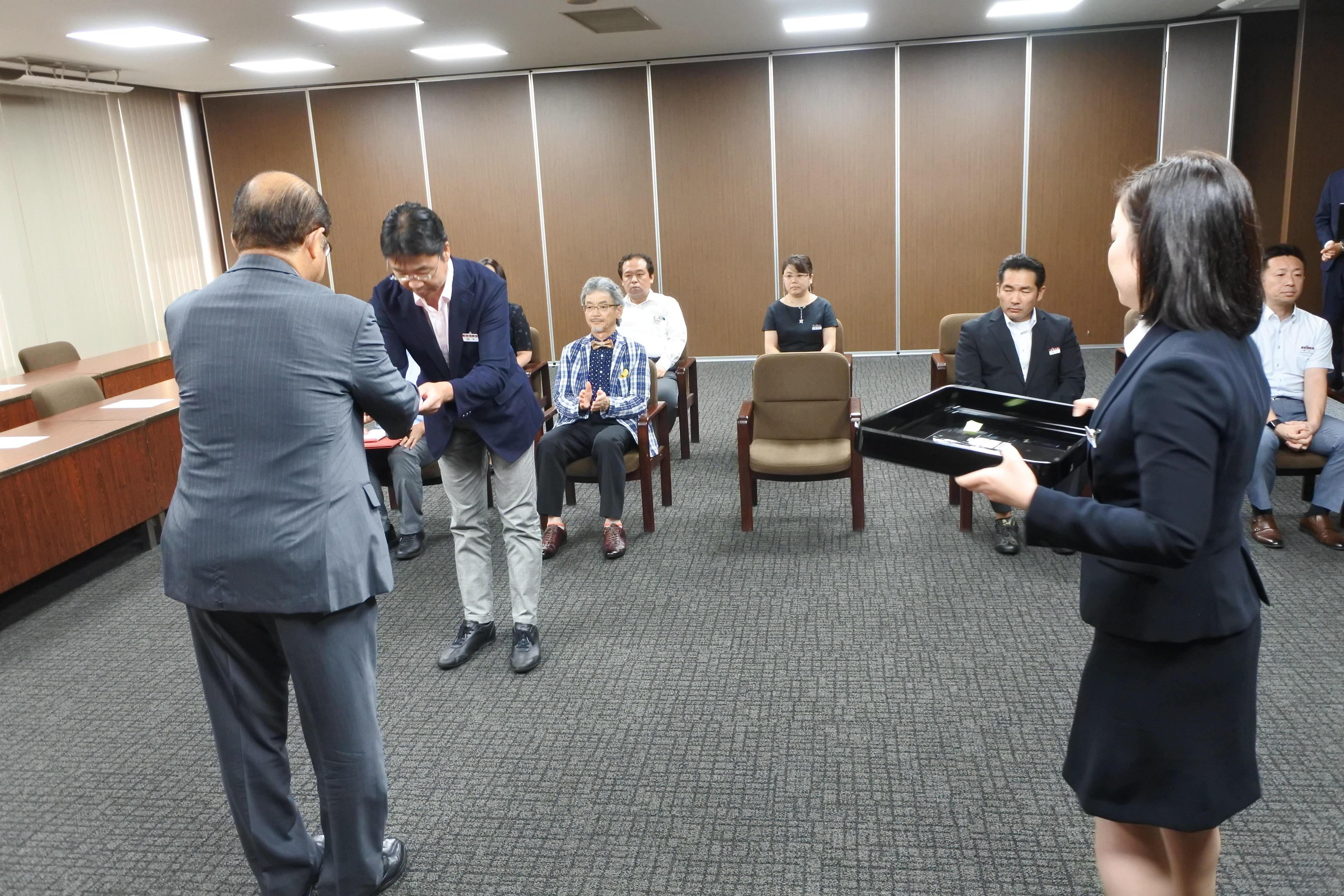 立花貞司理事長から記念品を受け取る梅本達弥財政部課長