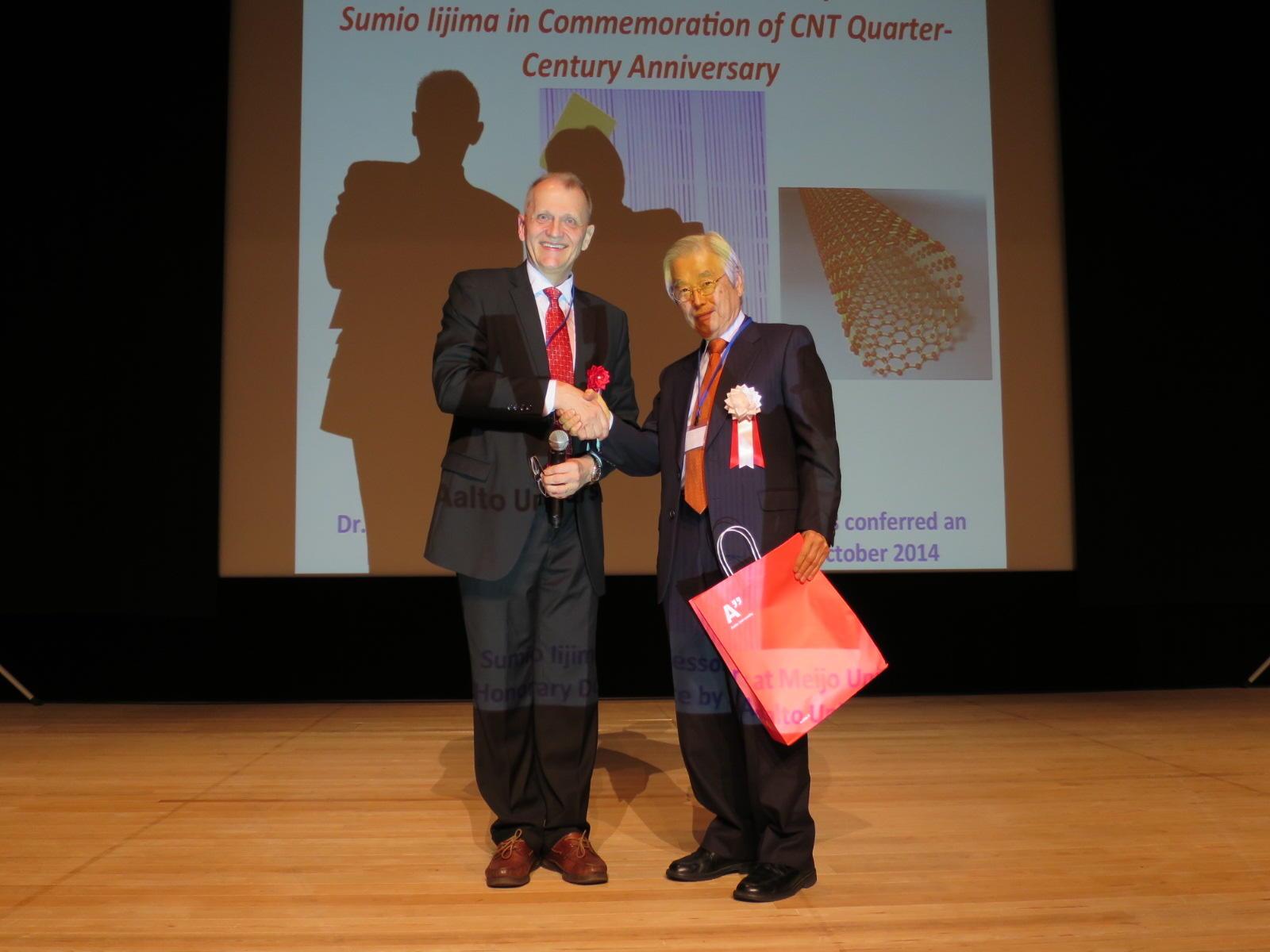 2016年11月のカーボンナノチューブ発見25周年の国際会議で握手する飯島終身教授(右)とカウピネン氏