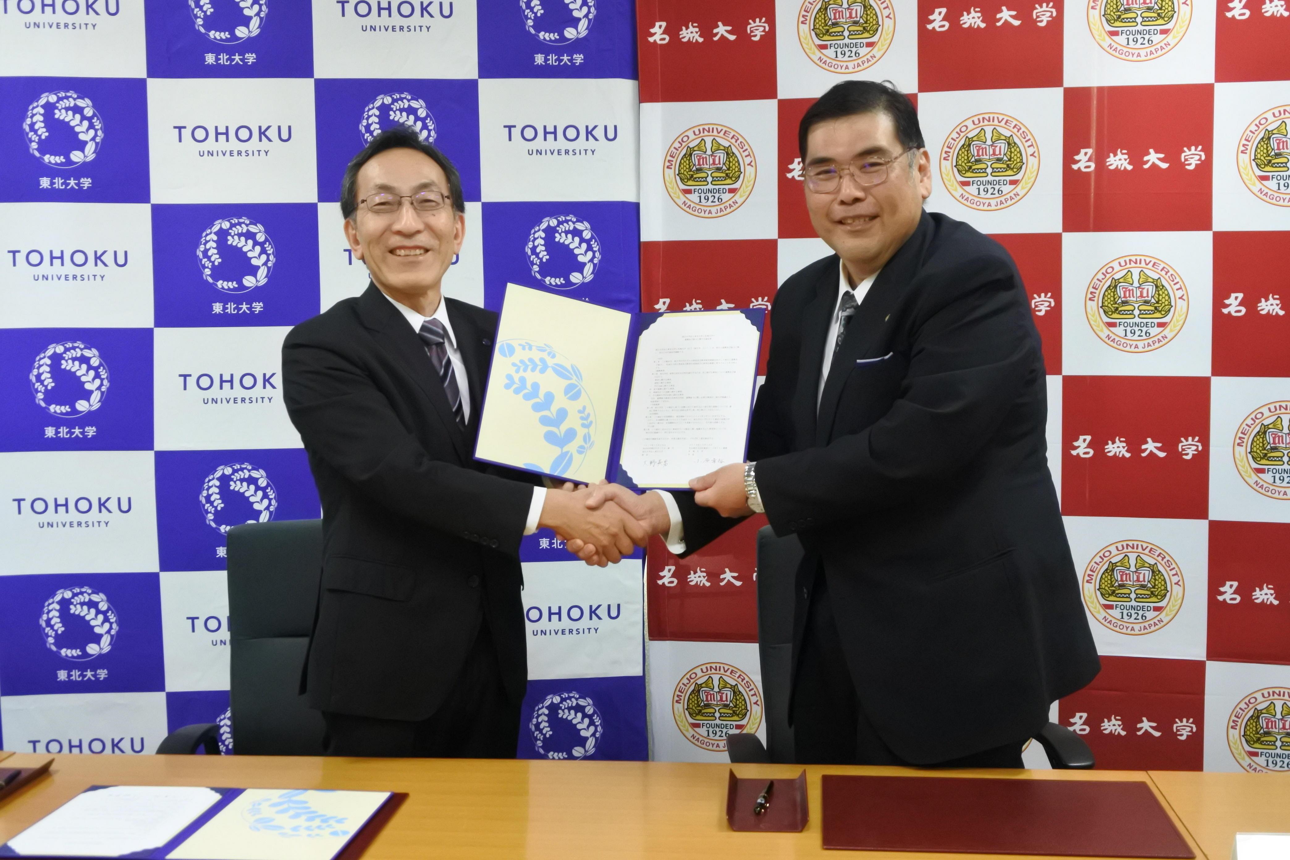 協定書を手に握手する小原章裕学長(右)と大野英男総長
