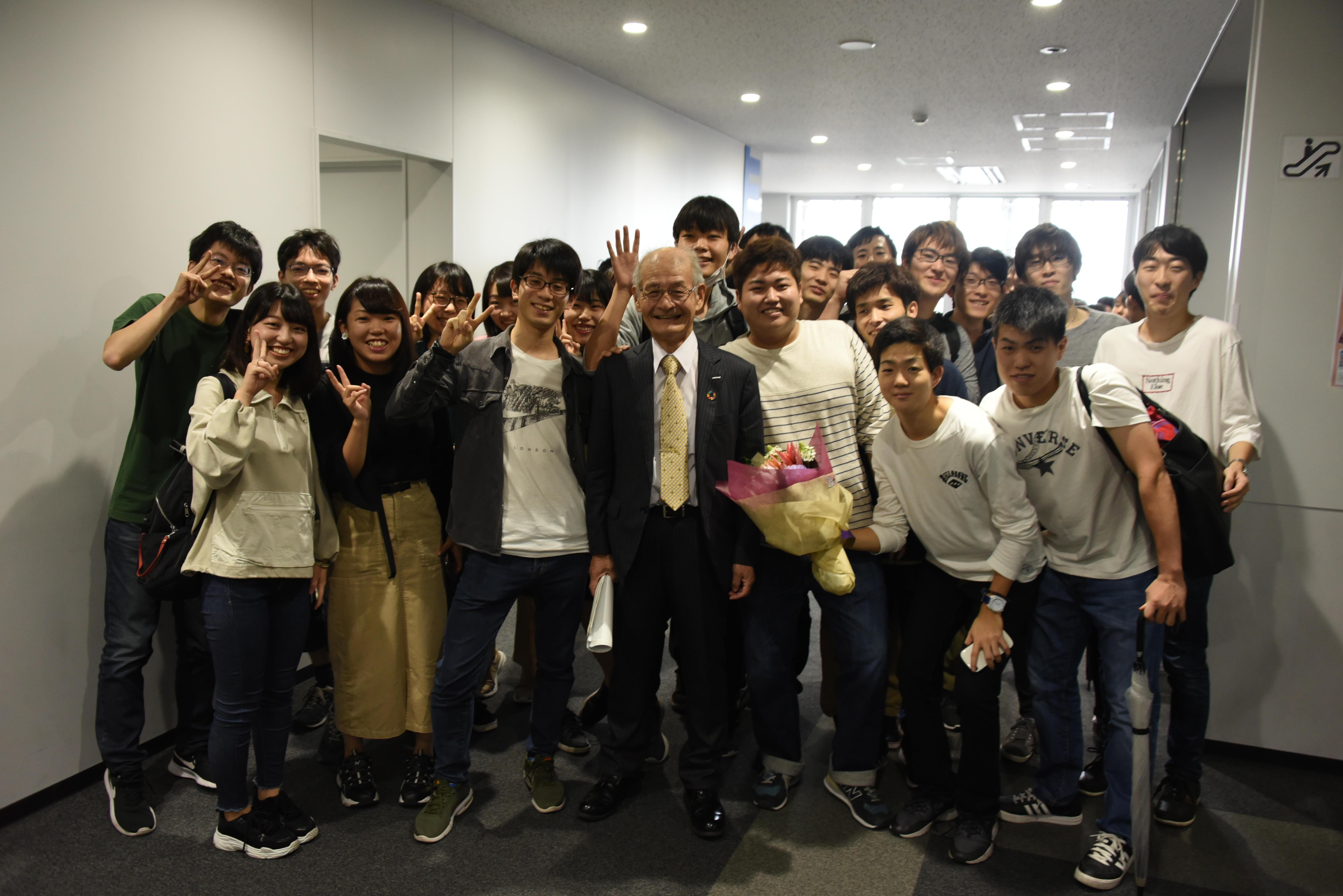 共通講義棟東で学生たちに囲まれる吉野教授
