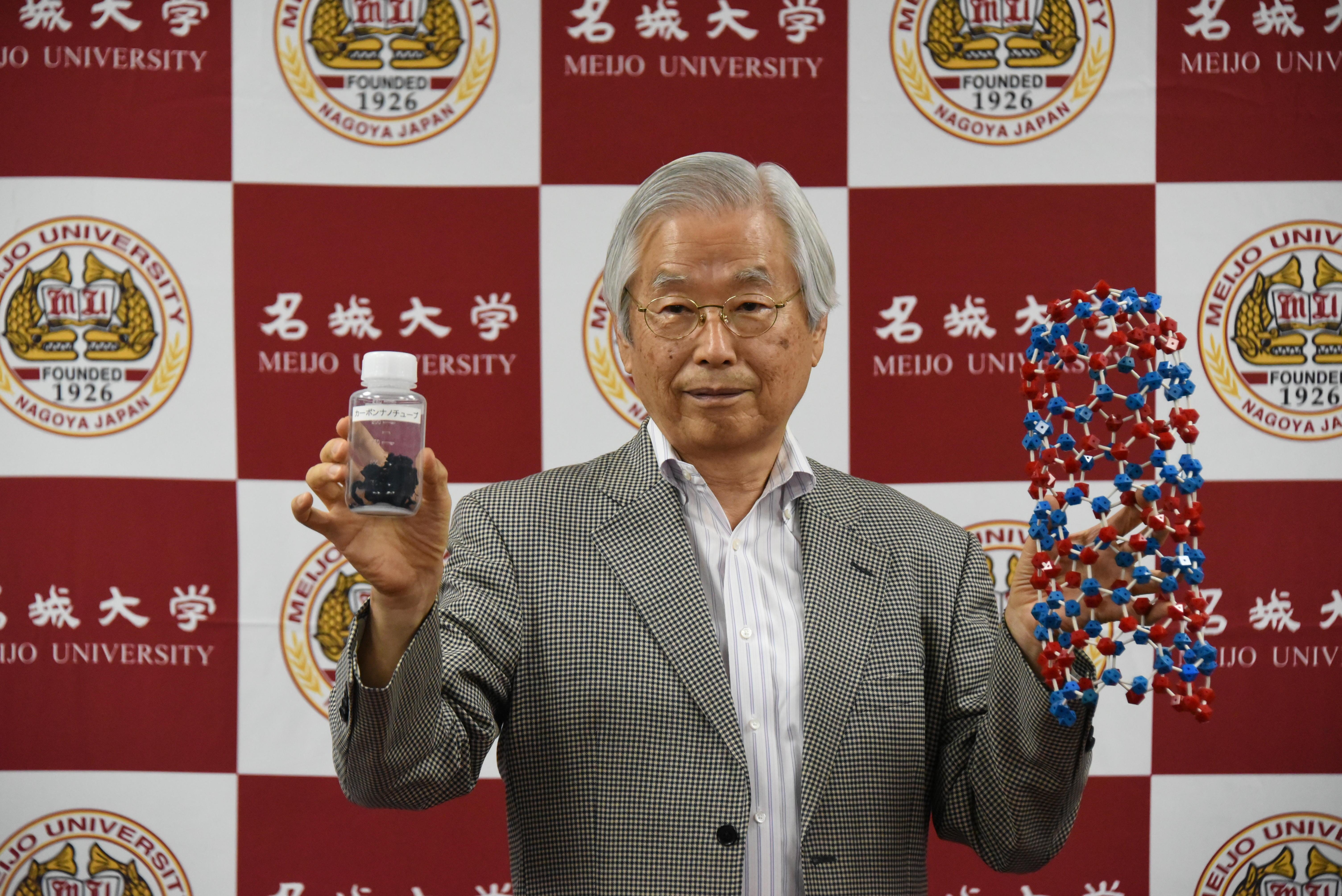 カーボンナノチューブと模型を持つ飯島澄男終身教授