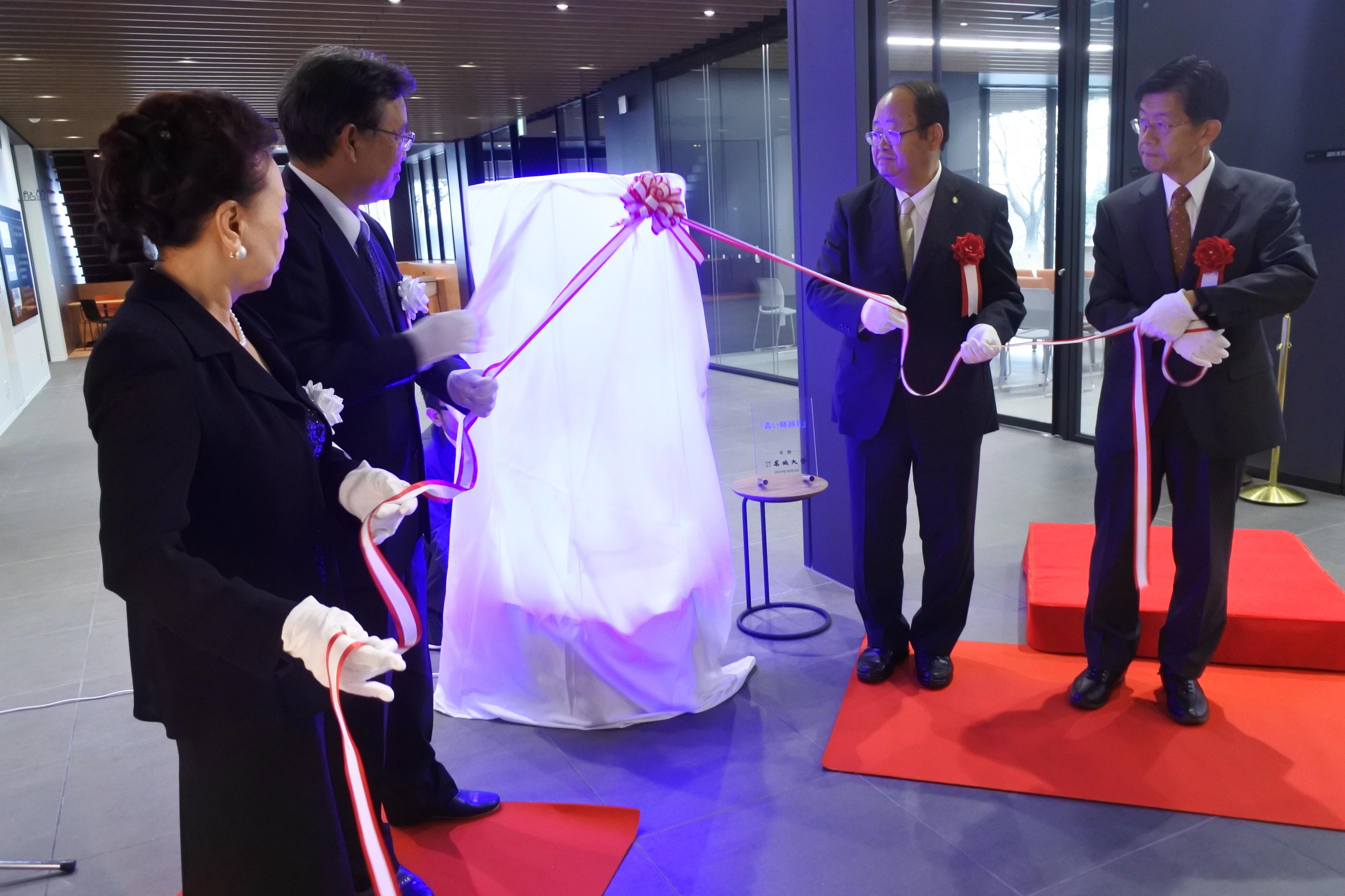 「青い輝跡Ⅱ」を除幕する(左から)神野公子名誉理事長、山田弘幸理事長、立花貞司理事長、平松正行理事