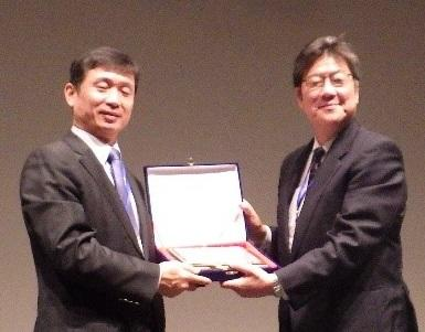 キム・ジンマン会長から感謝状を受け取る道正教授(右)