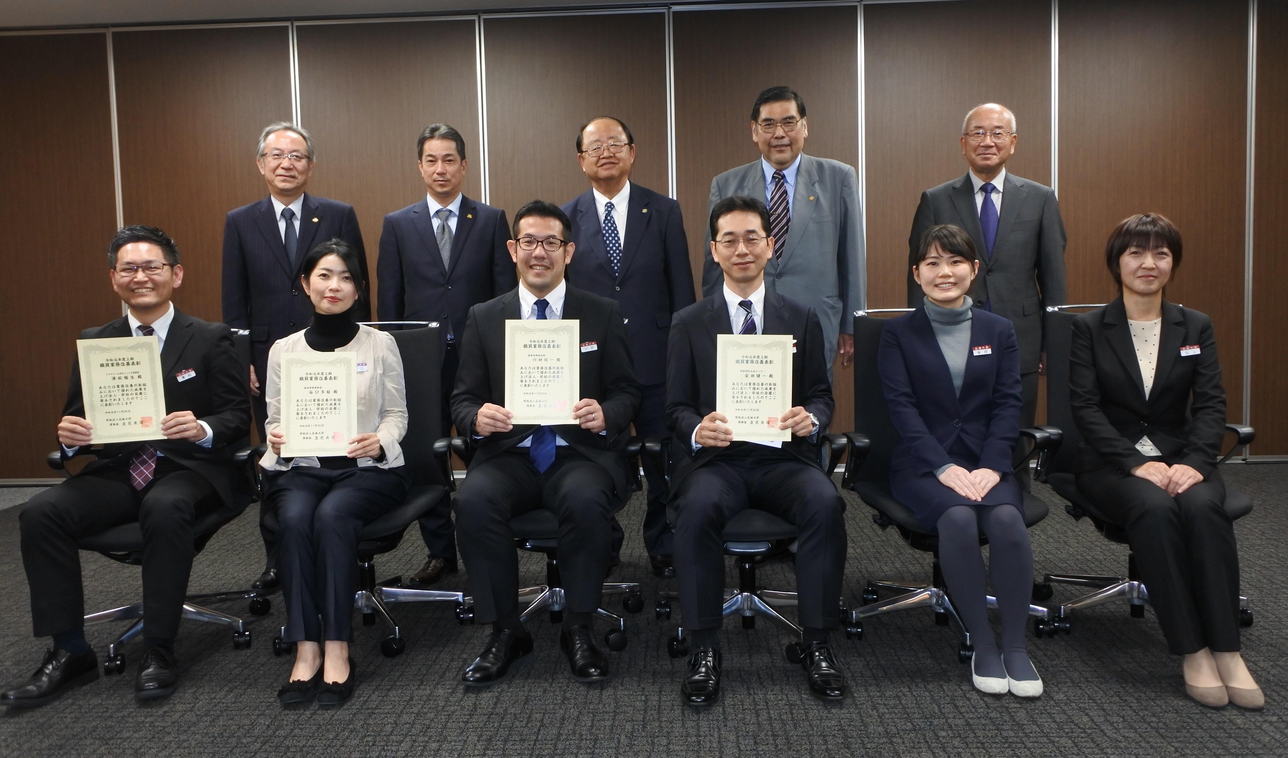 表彰状を手にする職員と立花貞司理事長ら