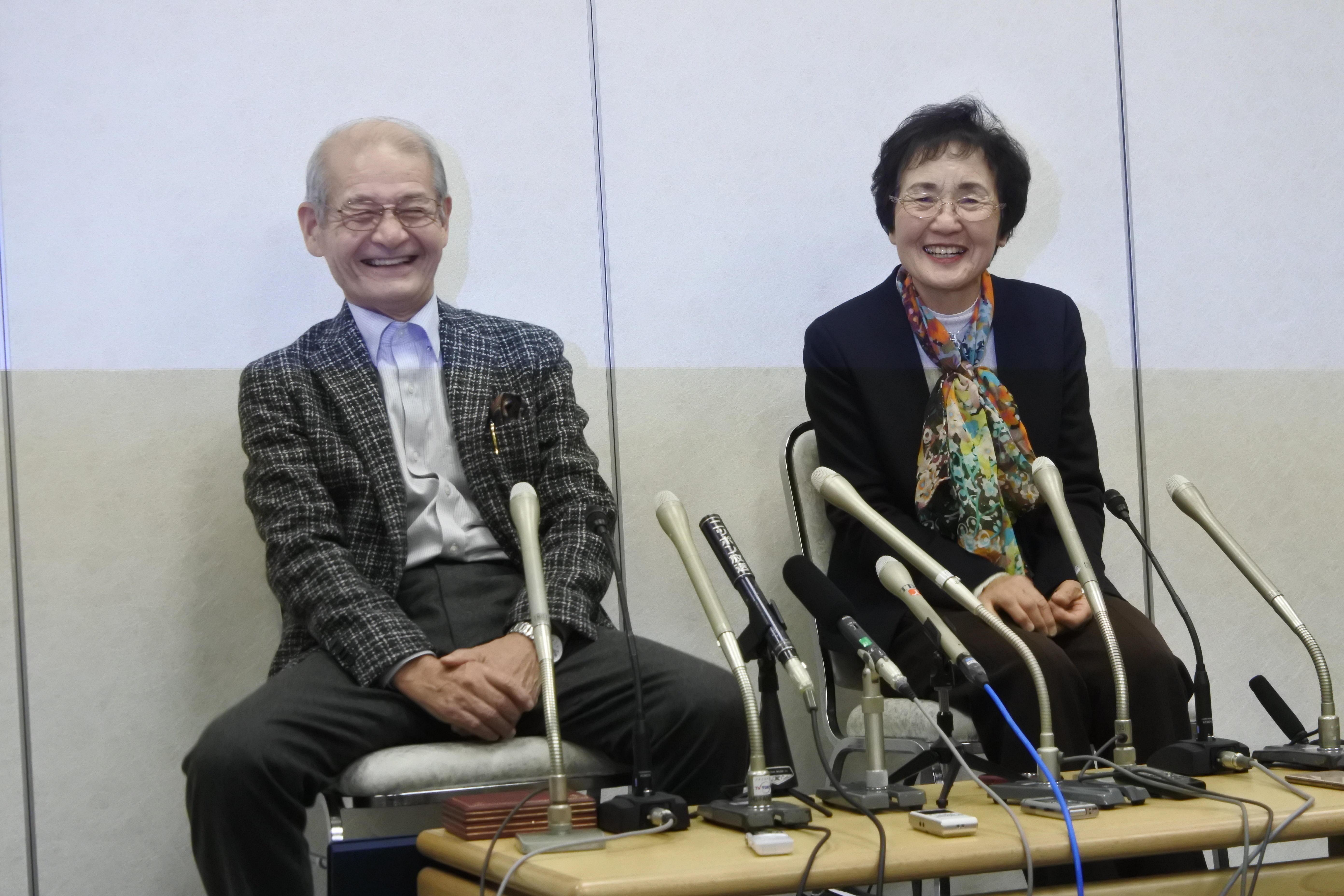 笑顔で記者会見する吉野教授(左)と久美子夫人
