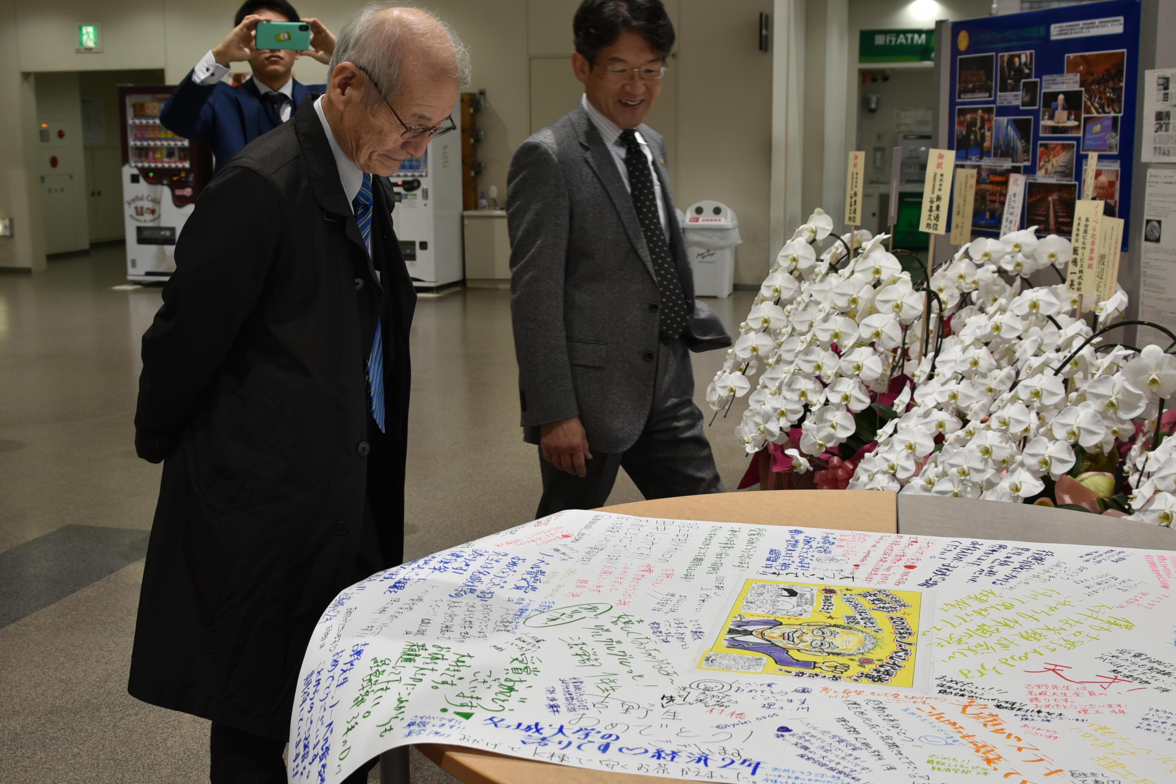 祝賀ブースに置かれた学生の寄せ書きを見る吉野教授