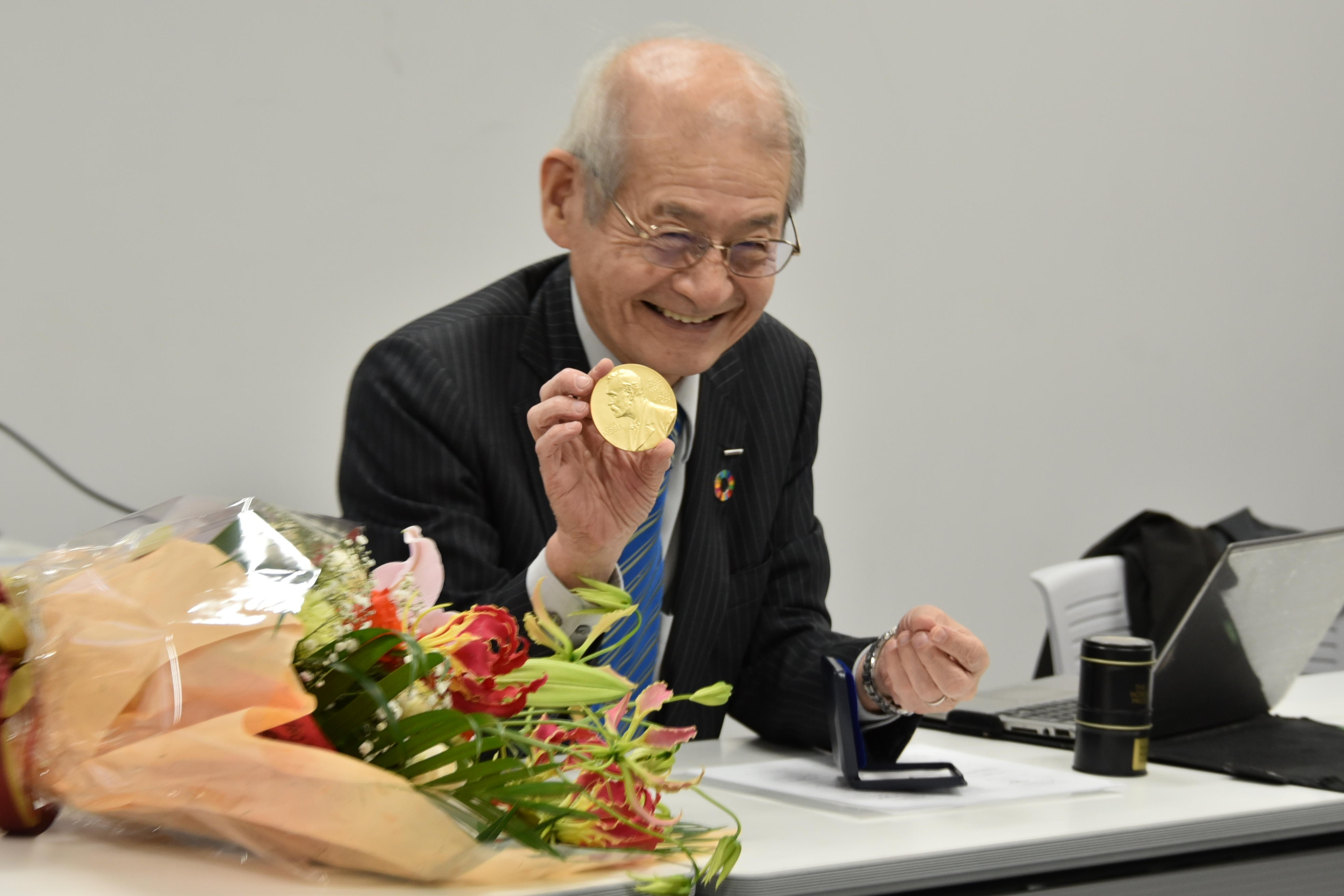 ノーベル賞のメダルを見せる吉野教授
