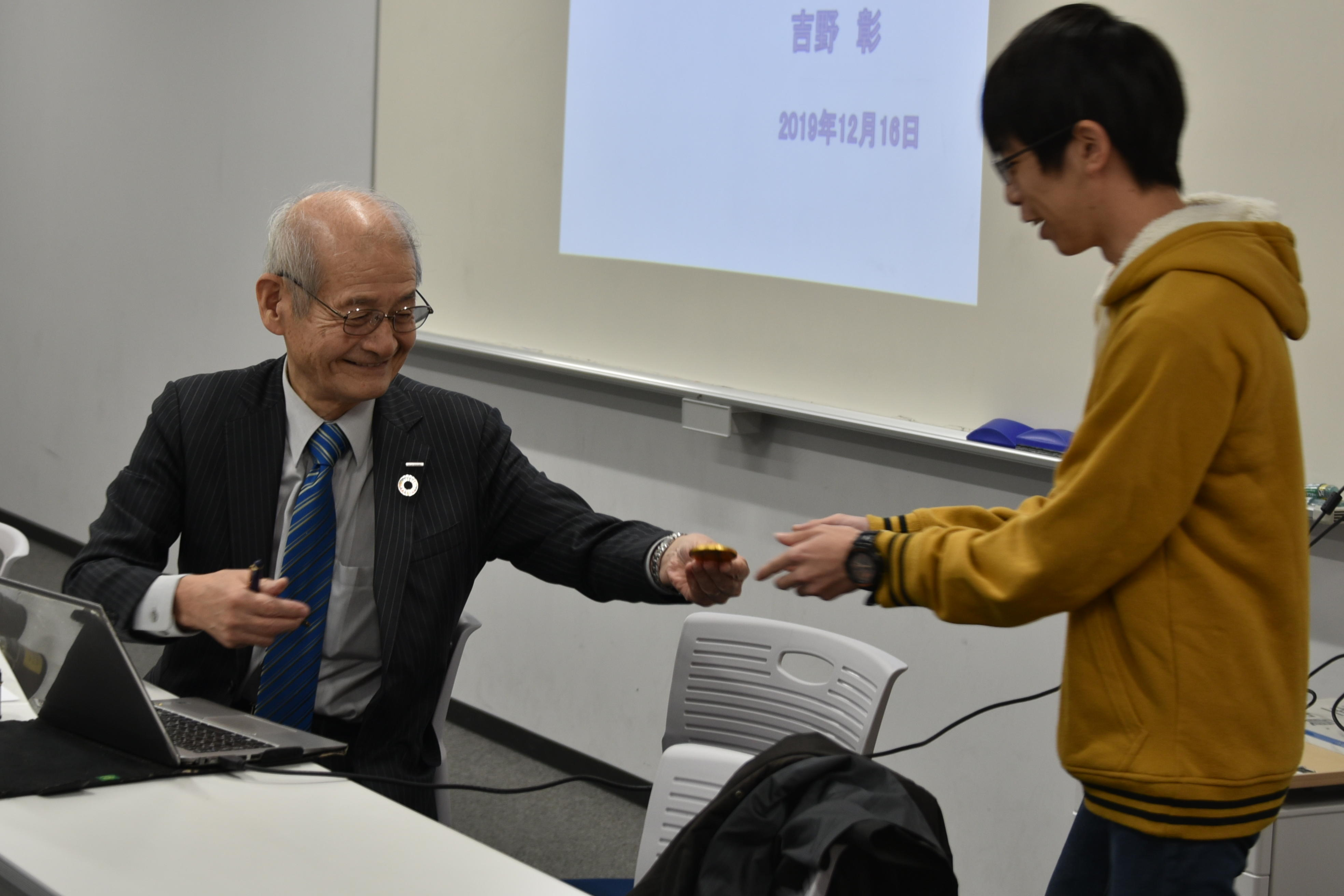 メダルチョコにサインし、一人一人に手渡す吉野教授