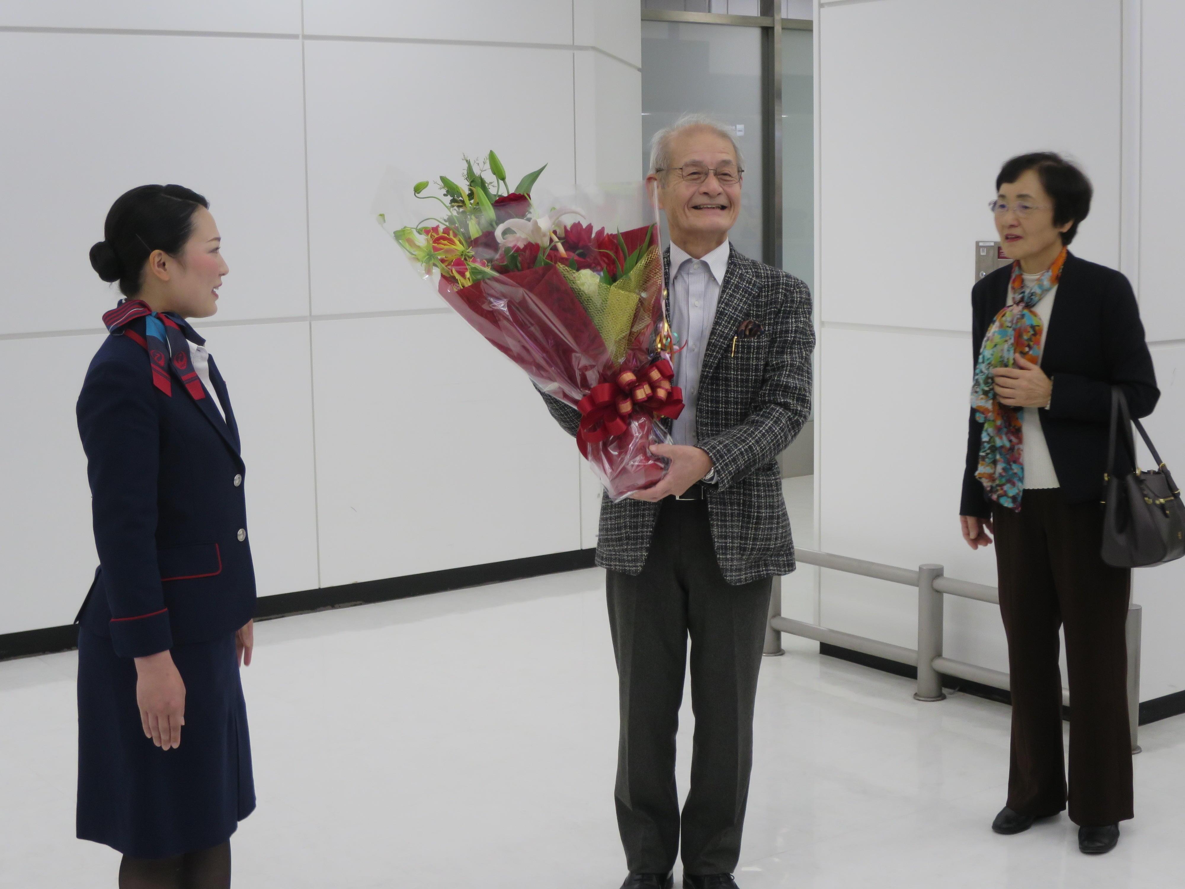 成田空港で花束贈呈を受けた吉野教授