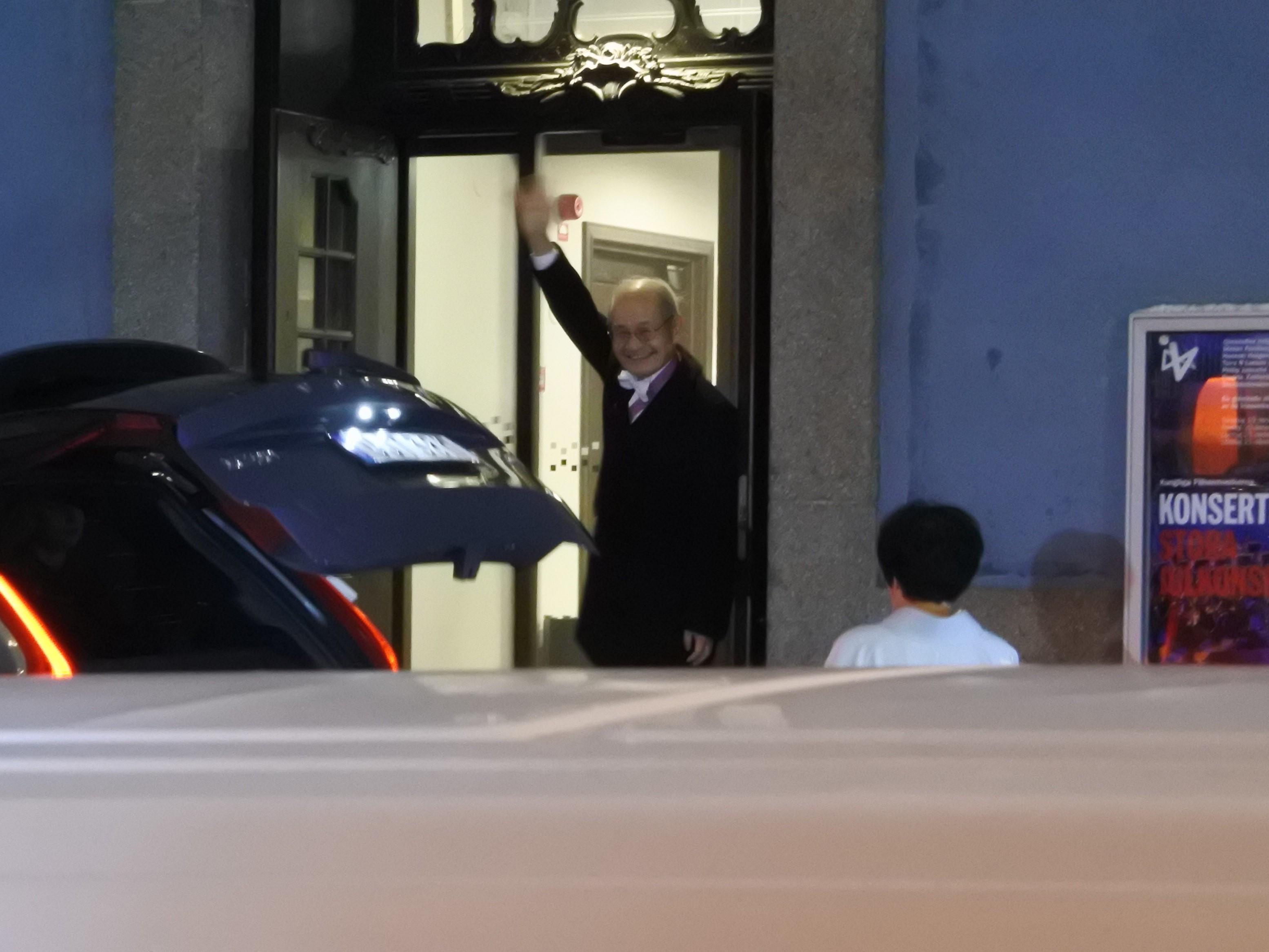 授賞式会場のストックホルムコンサートホールに入る際、報道陣の呼びかけに手を振って応える吉野教授。現地でもサービス精神は欠かさなかった