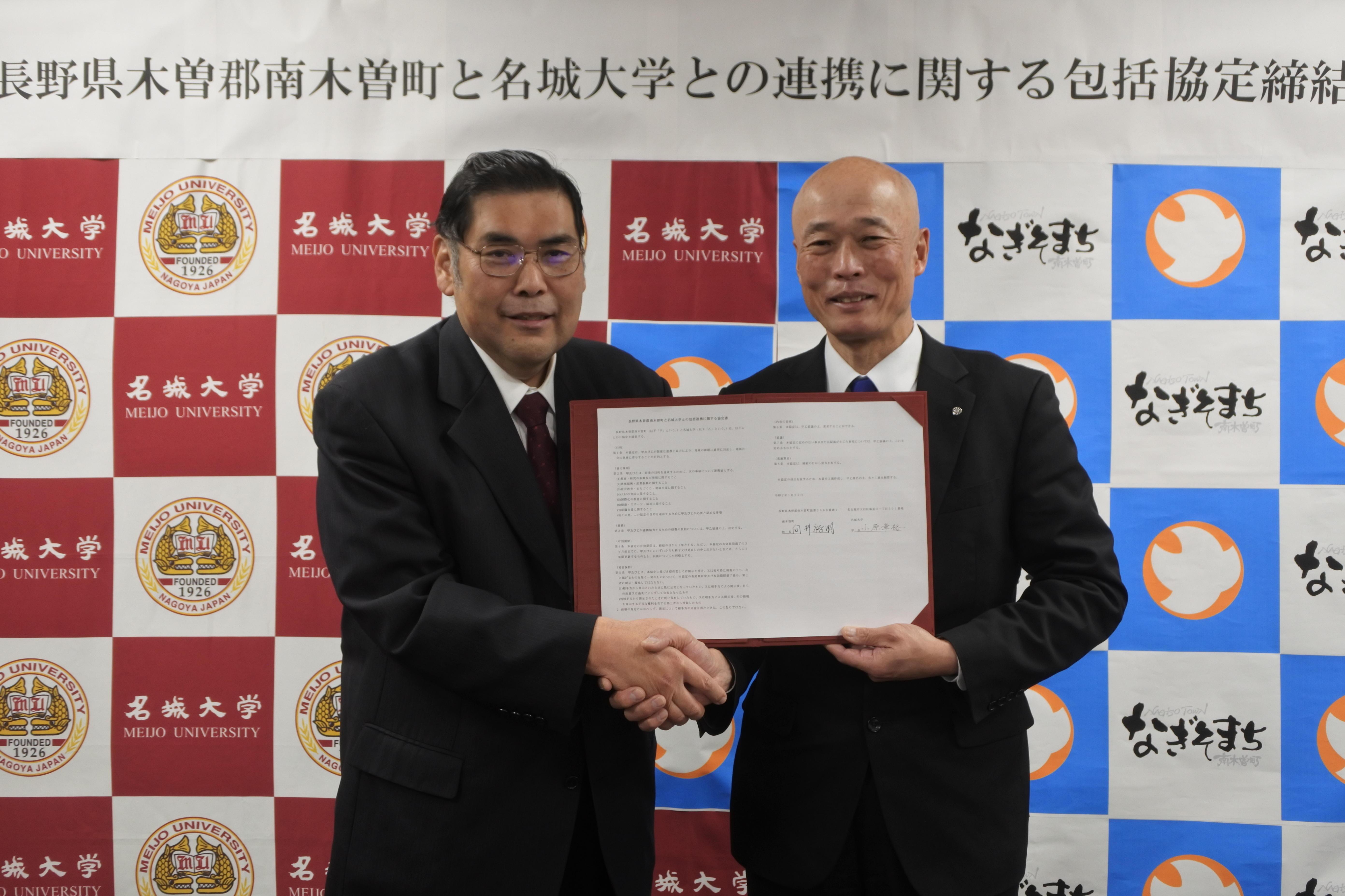 協定書を手に握手する小原章裕学長(左)と向井裕明町長
