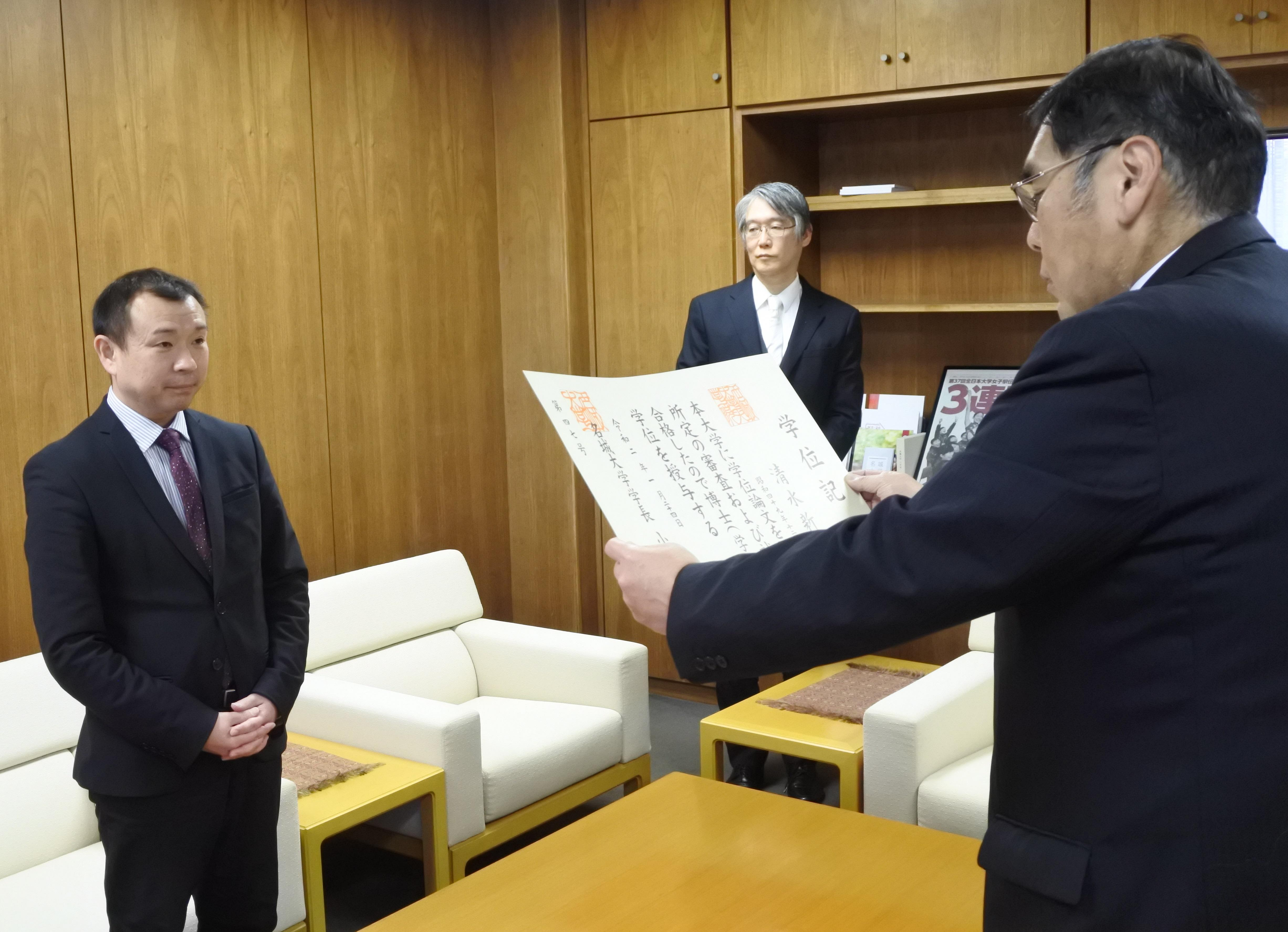 小原章裕学長から学位記を受け取る清水新悟さん(左)