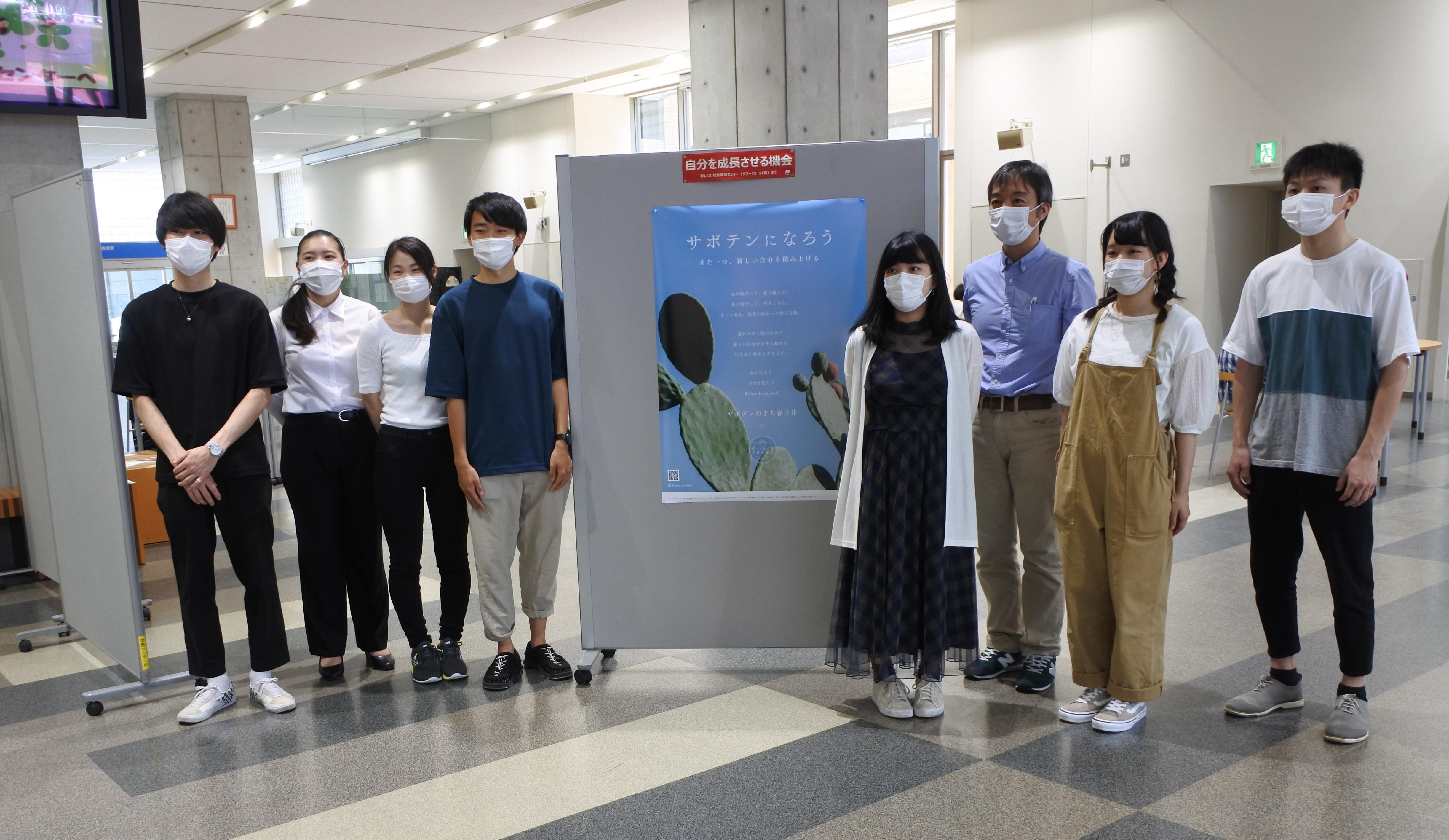 タワー75の学生ホールにポスターを掲示した近藤准教授と学生たち