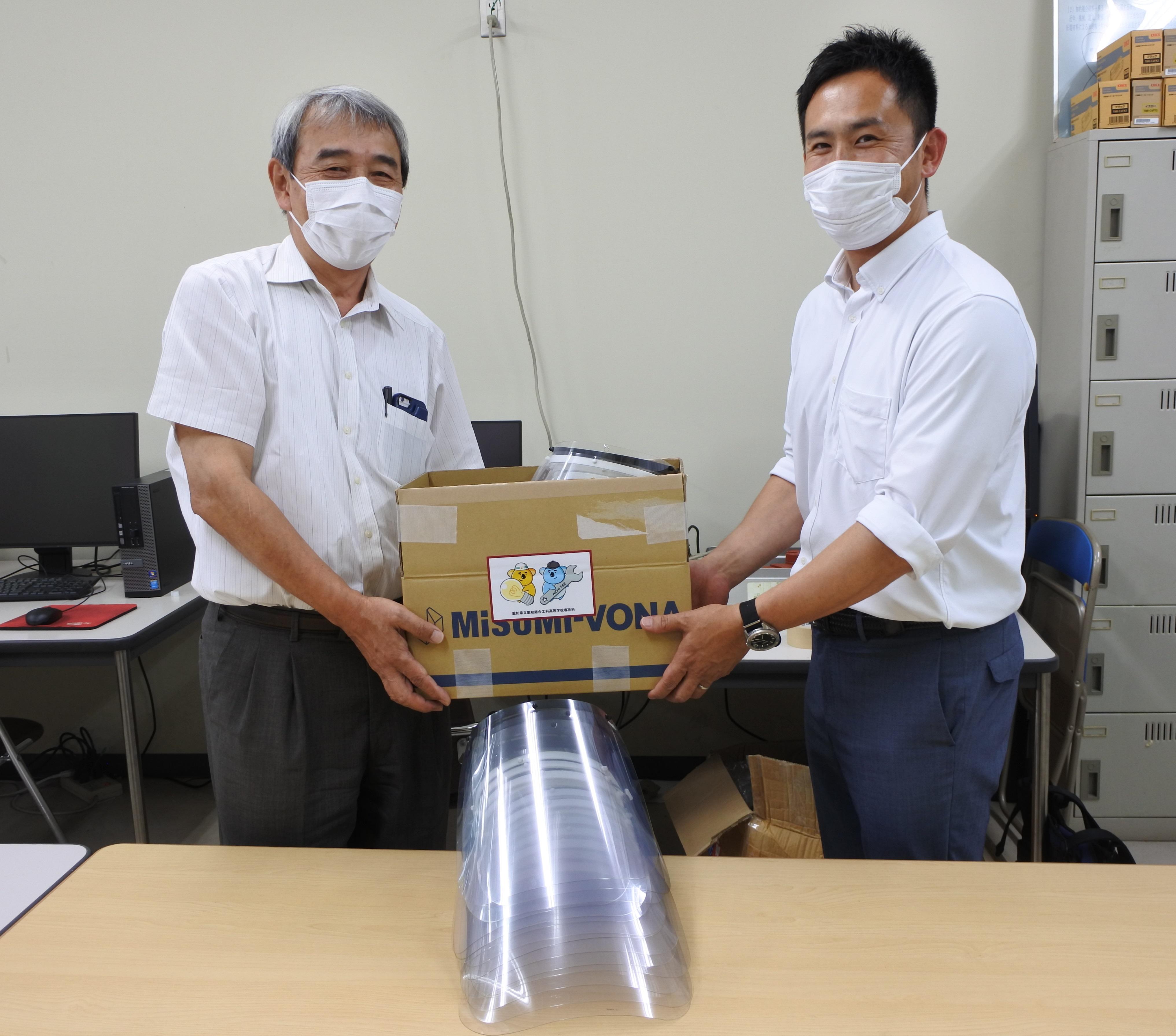 加鳥教授(左)にフェイスシールドを手渡す西村さん
