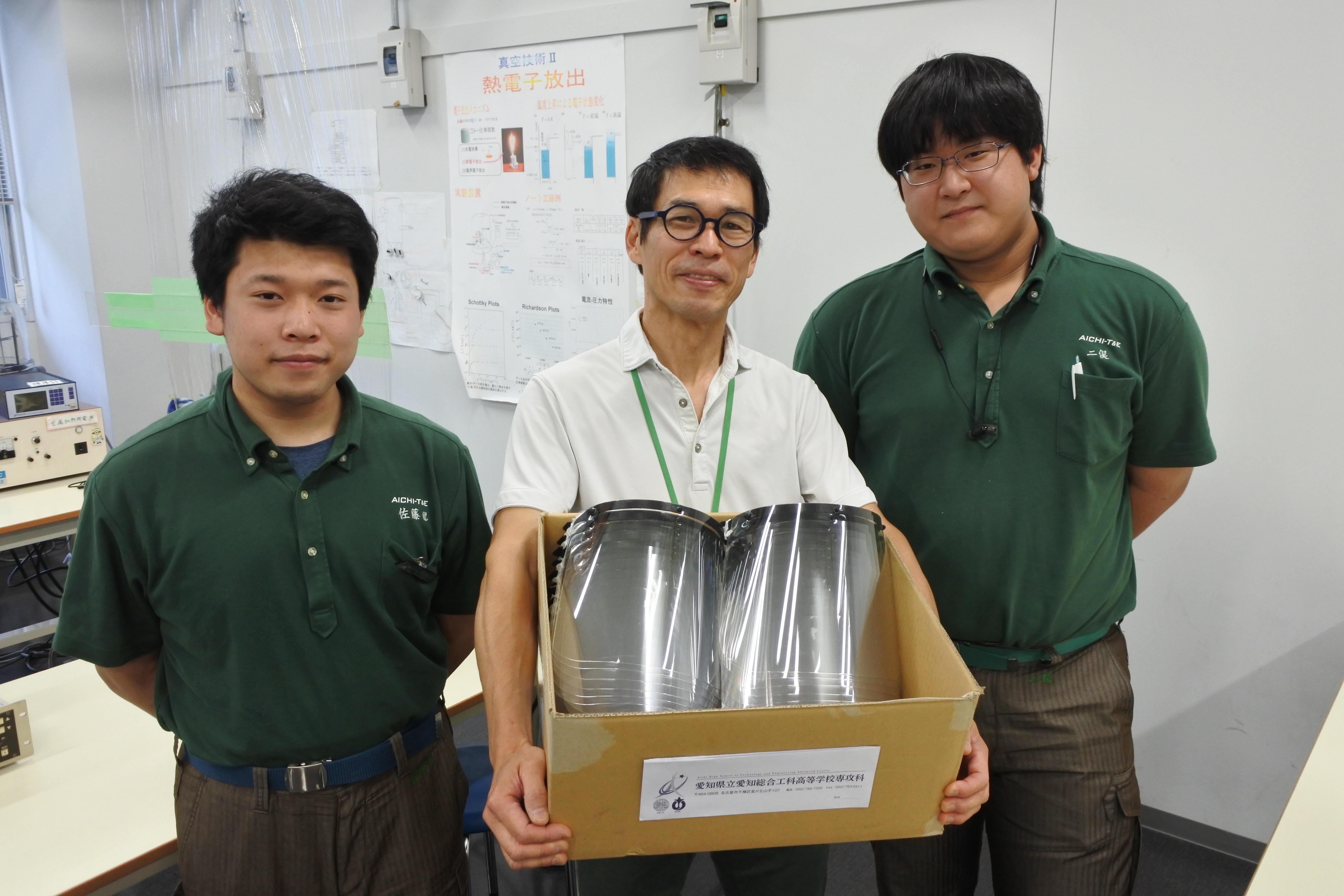 フェイスシールドを受け取った六田教授(中央)と、製作した二俣さん(右)と佐藤さん(左)