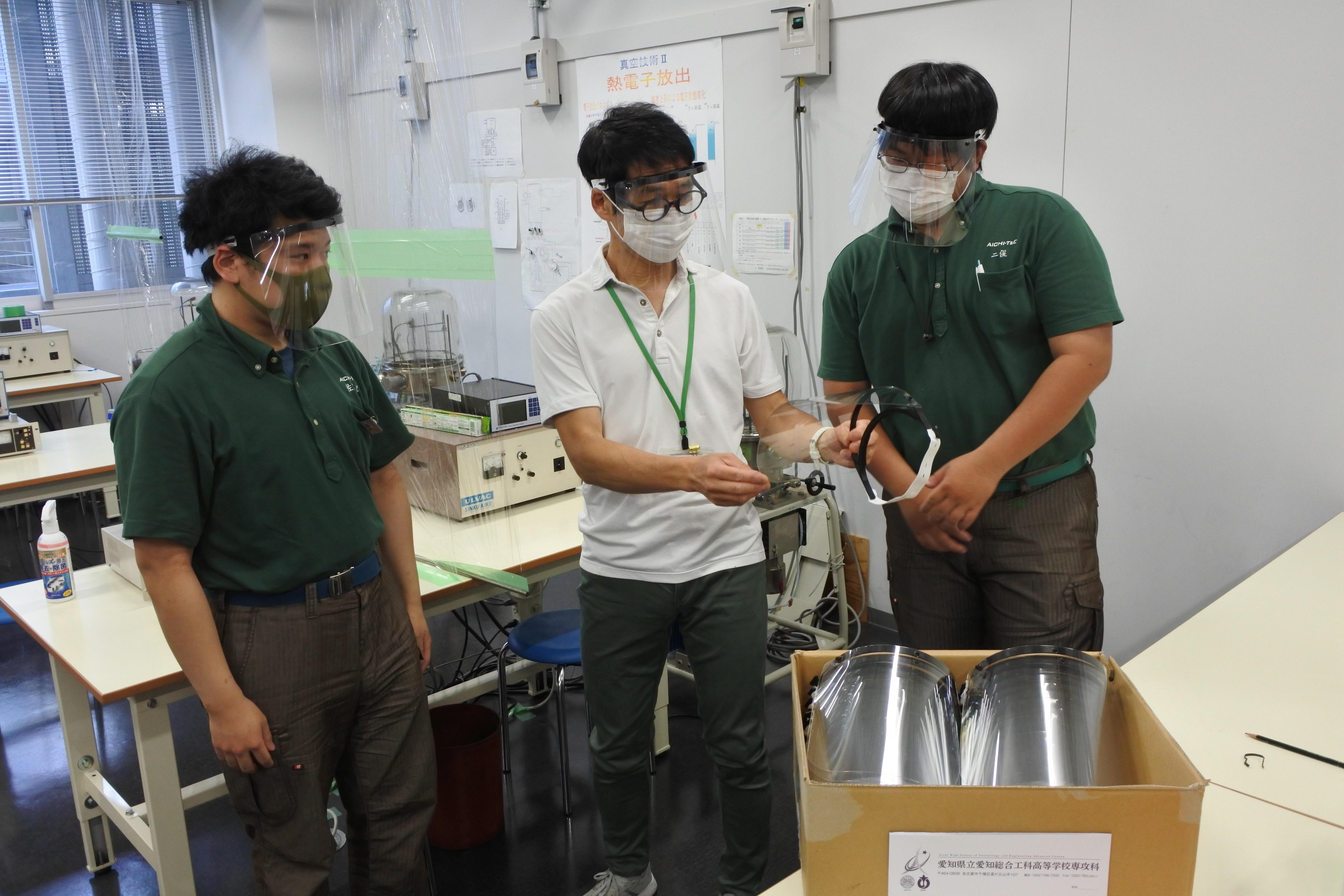 愛知総合工科高校専攻科生から寄贈されたフェイスシールドの出来栄えを確かめる六田教授(中央)