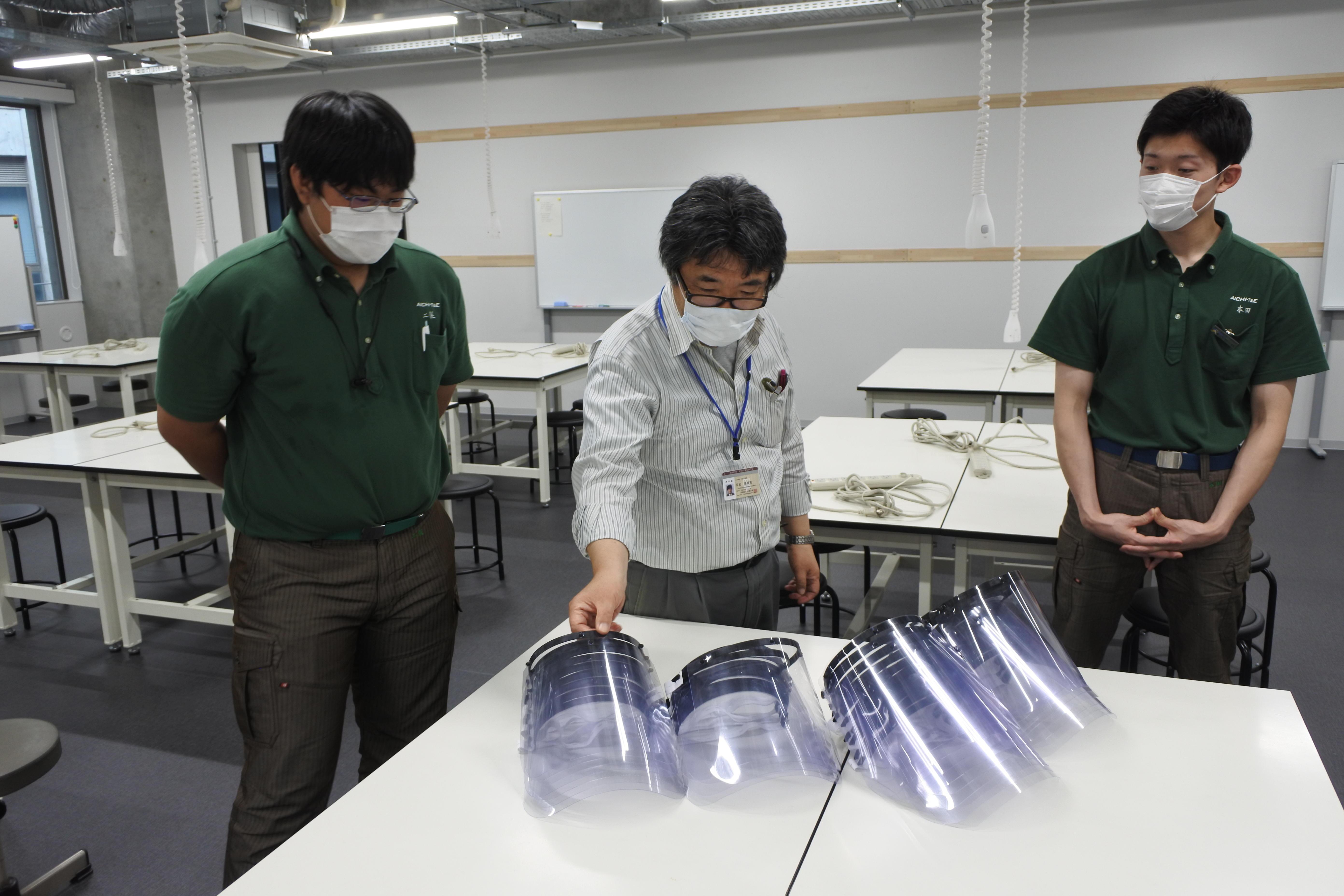 寄贈されたフェイスシールドと平松教授(中央)、本田さん(右)、二俣さん(左)