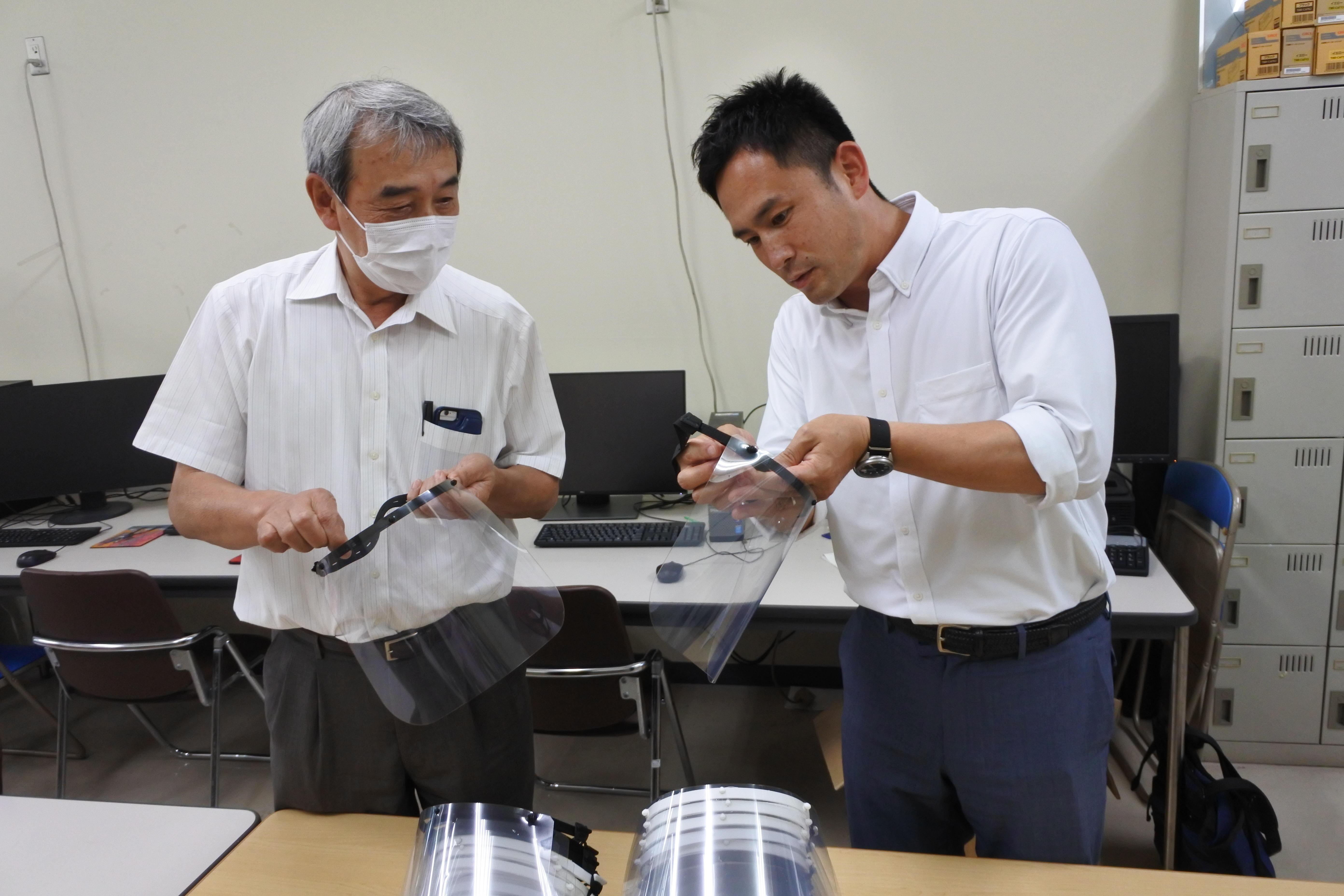 フェイスシールドを手に取ってみる加鳥教授(左)と西村さん