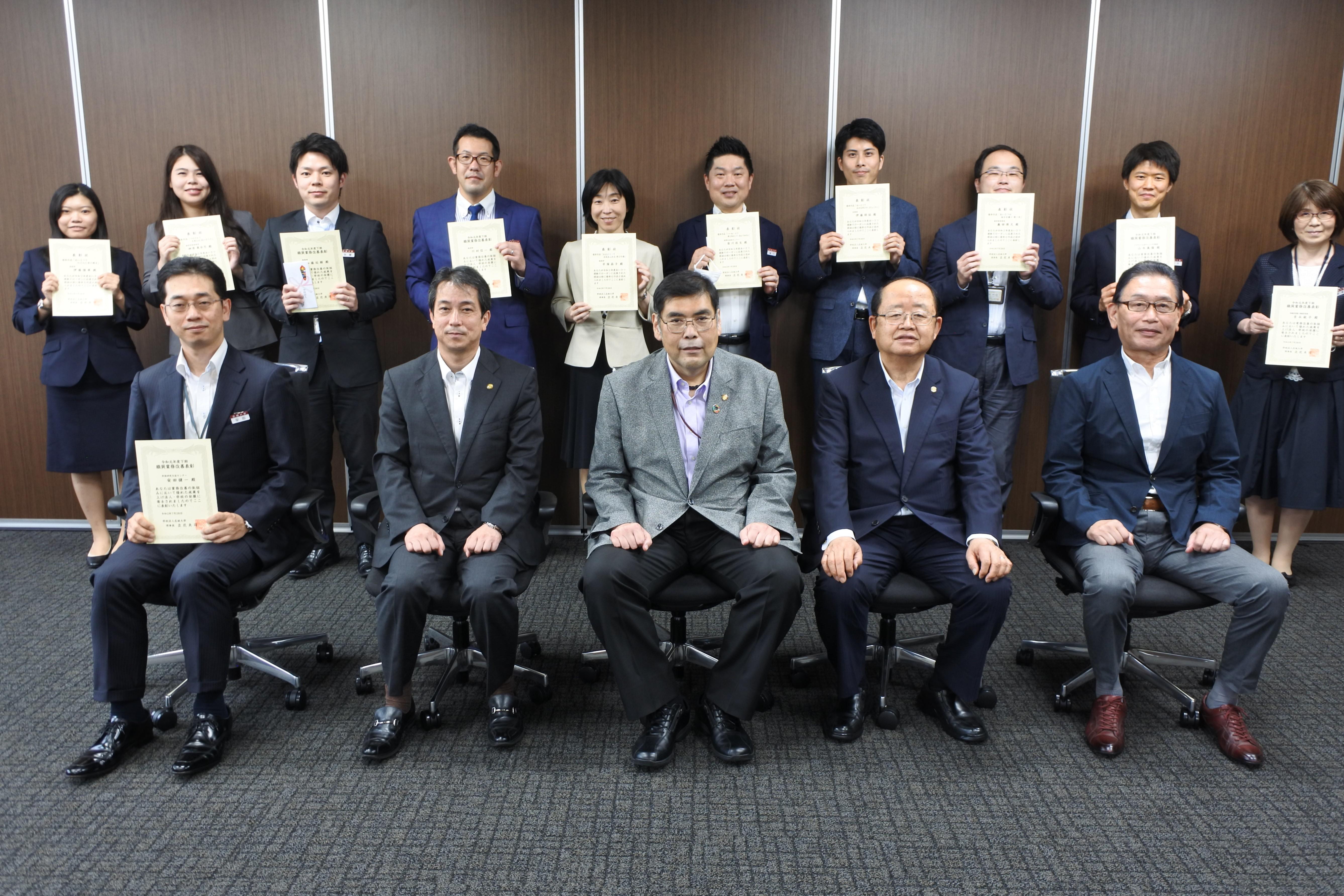 職員業務改善とあいさつ運動スローガンで表彰を受けた人たちと立花貞司理事長(前列右から2人目)ら