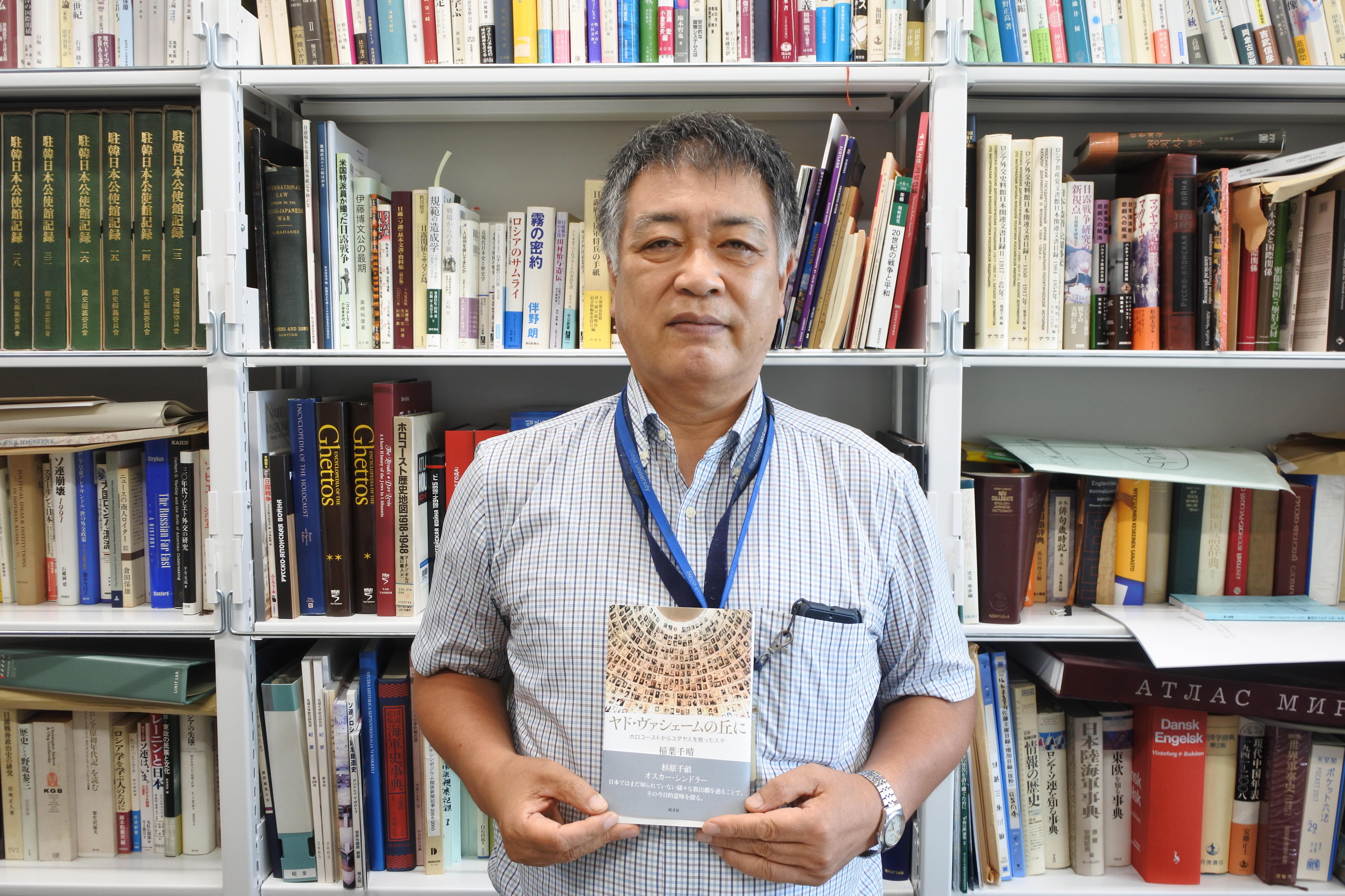 ナゴヤドーム前キャンパスの研究室で新著を手にする稲葉千晴教授
