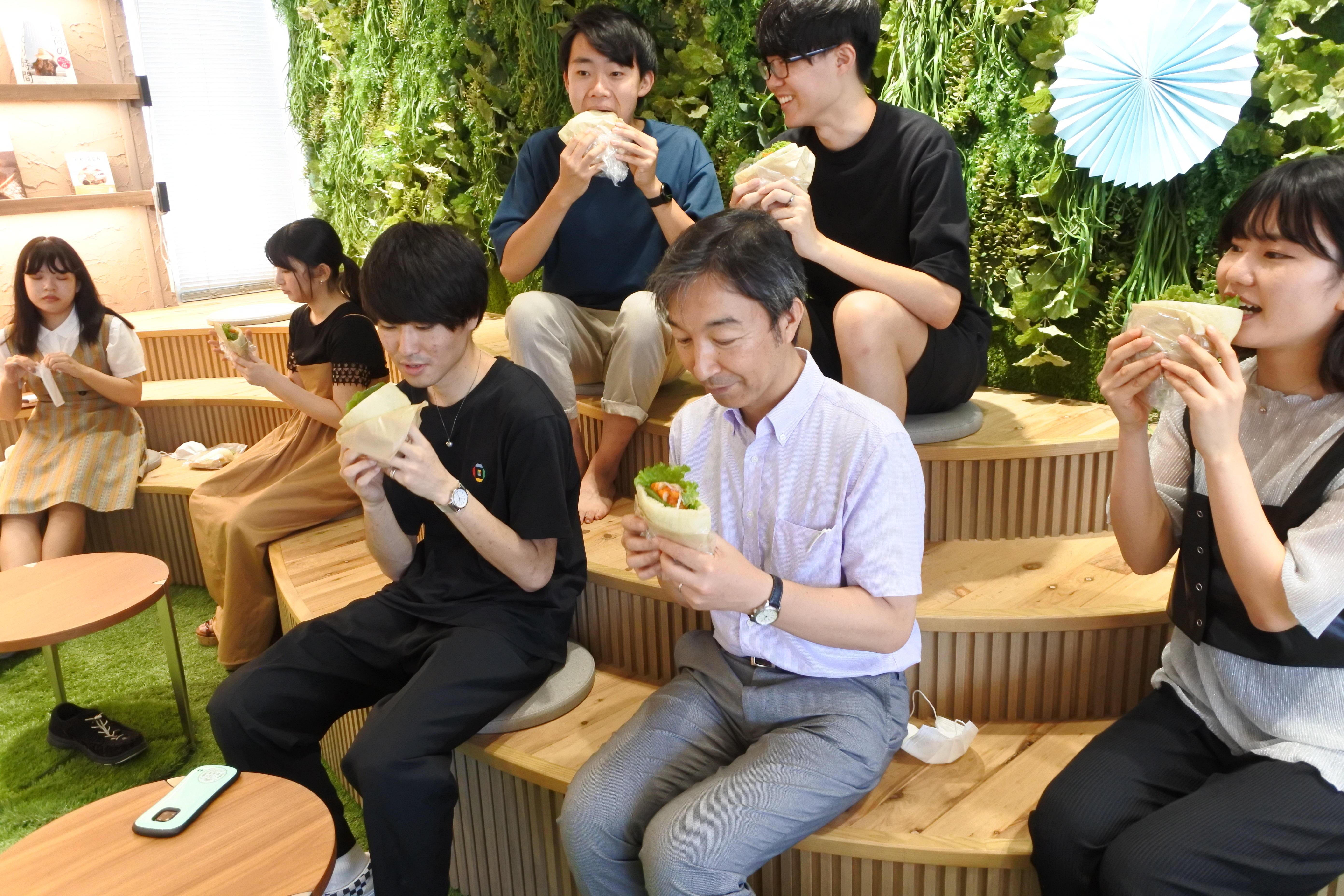 ピタパンサンド「エスニックサボーレ」を試食する近藤准教授(手前右から2人目)と学生たち