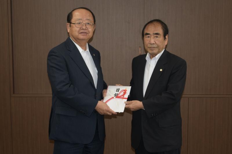 山田会長から立花理事長へ目録の贈呈(写真撮影のため、マスクをはずしています)