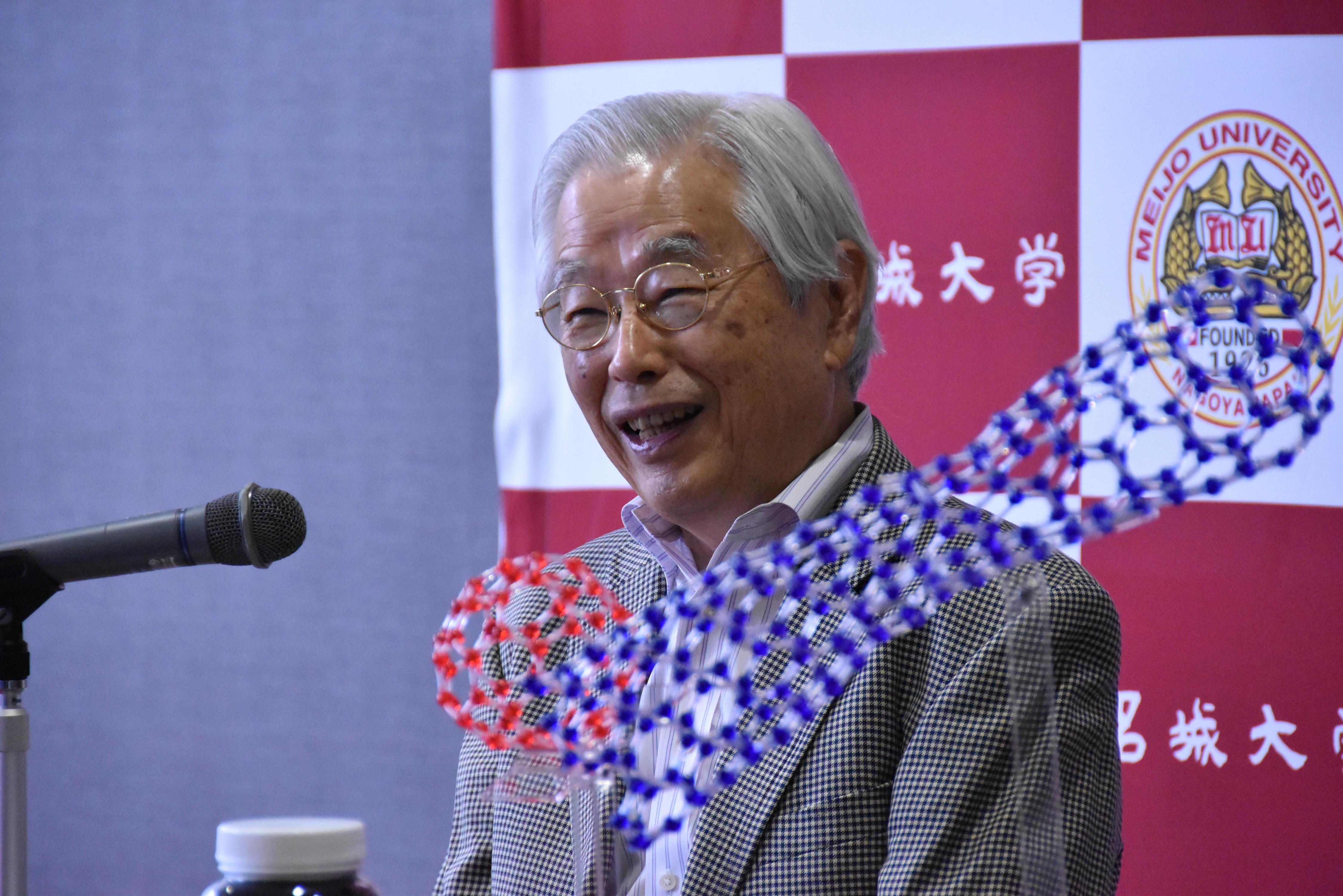 質問に答える飯島終身教授。手前右はカーボンナノチューブの模型