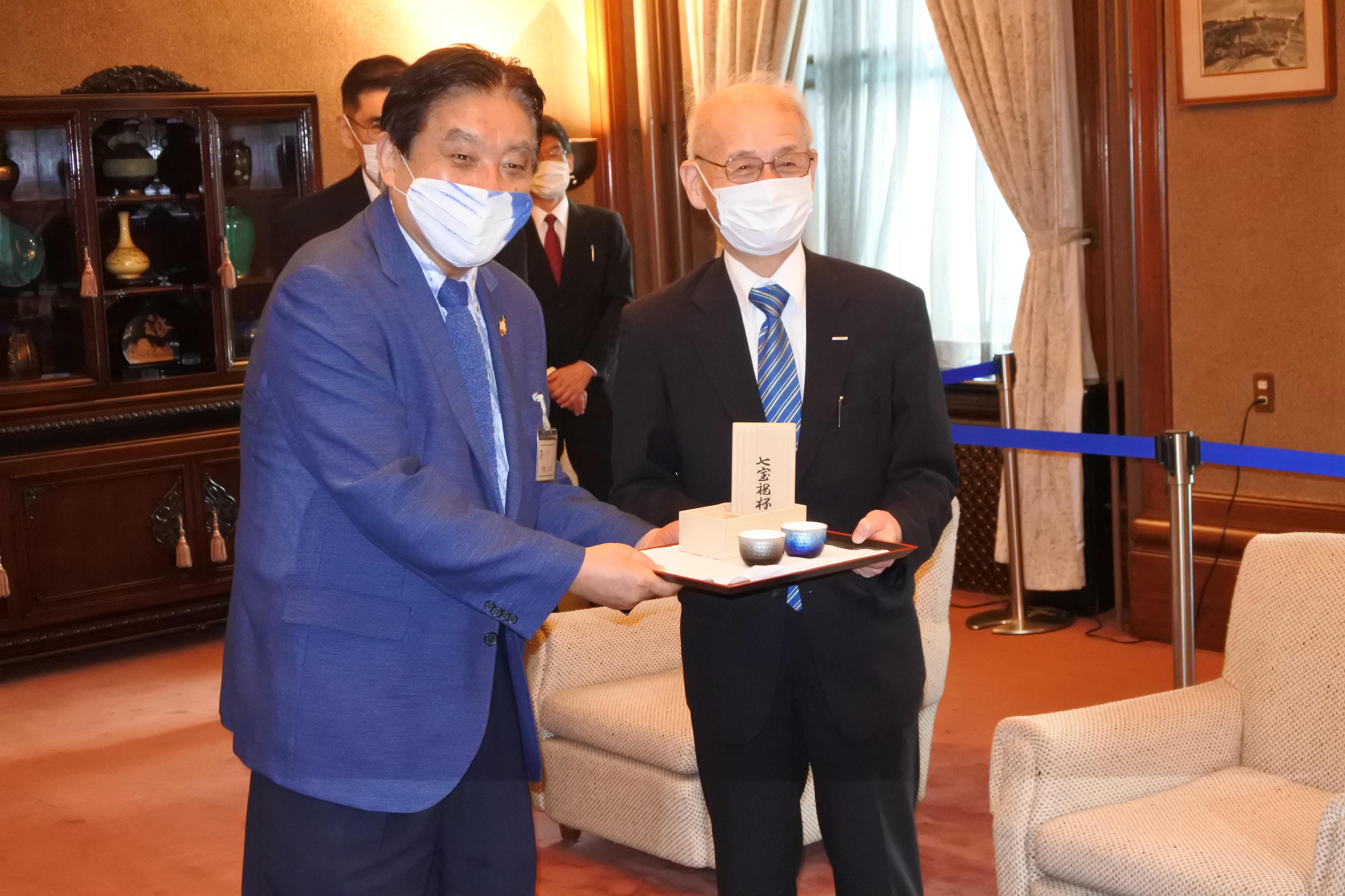 記念品の七宝祝杯を持って記念撮影する吉野教授と河村市長