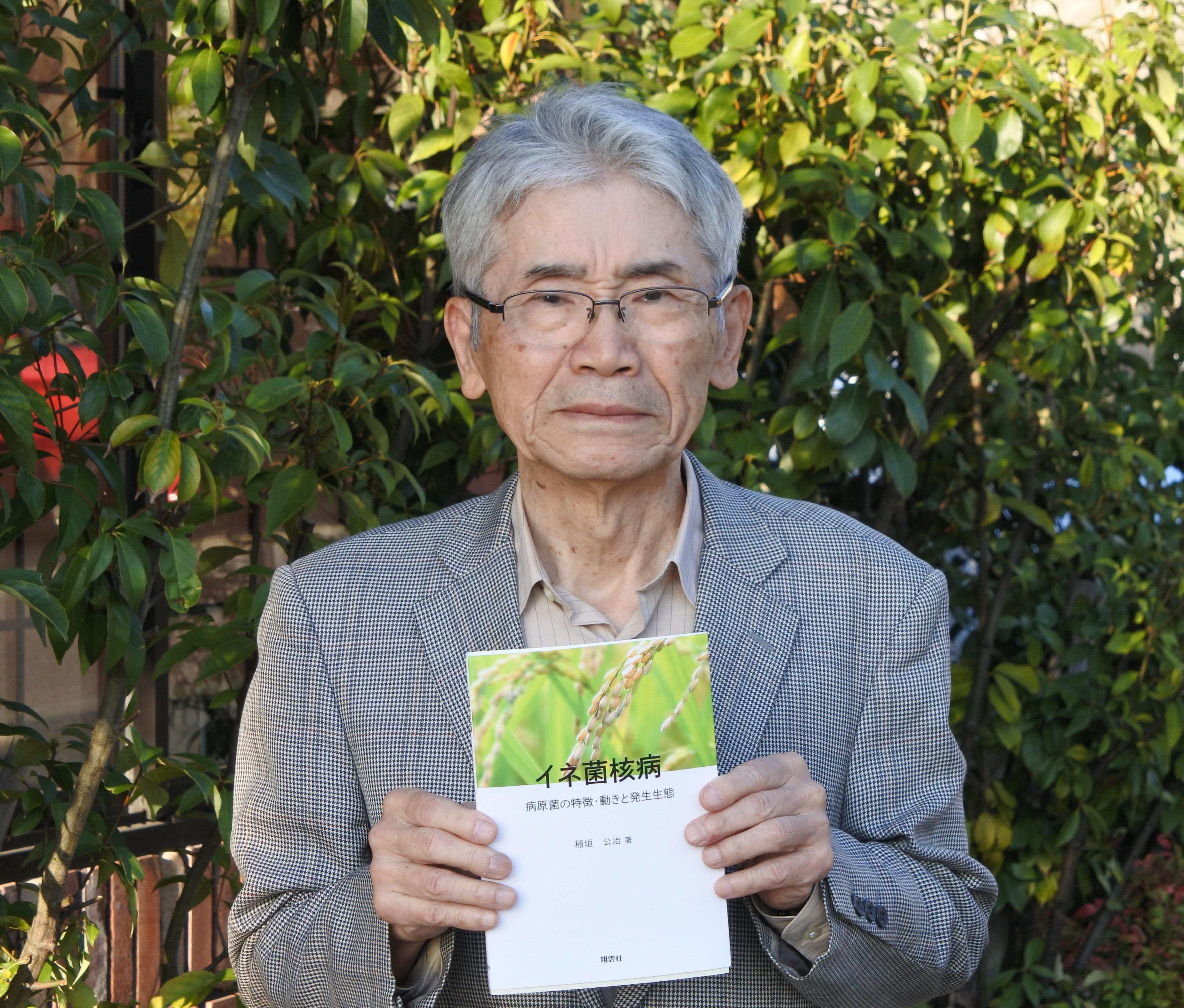 近著「イネ菌核病 病原菌の特徴・動きと発生生態」を手にする稲垣公治名誉教授