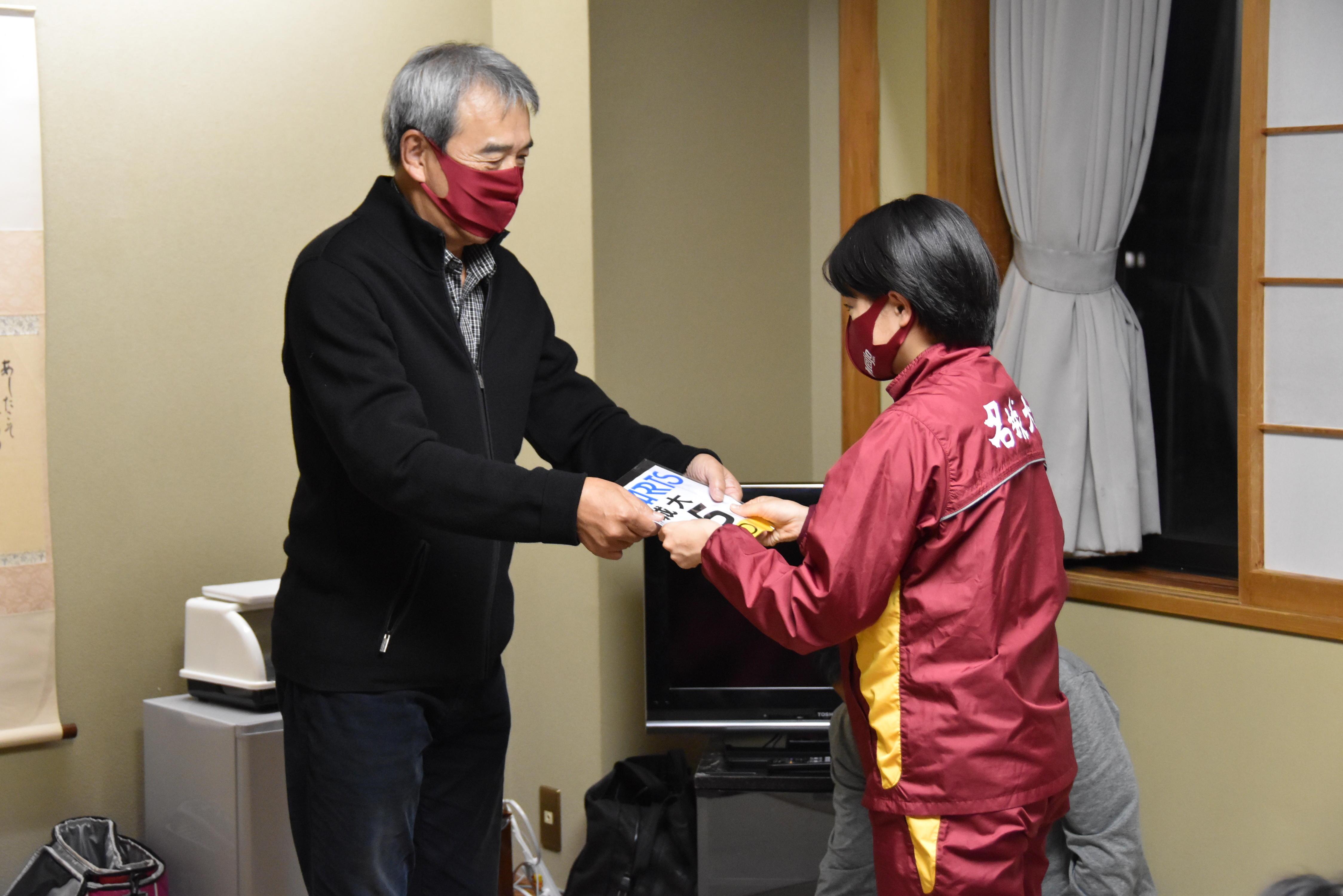 加鳥部長からゼッケンを手渡される加世田選手