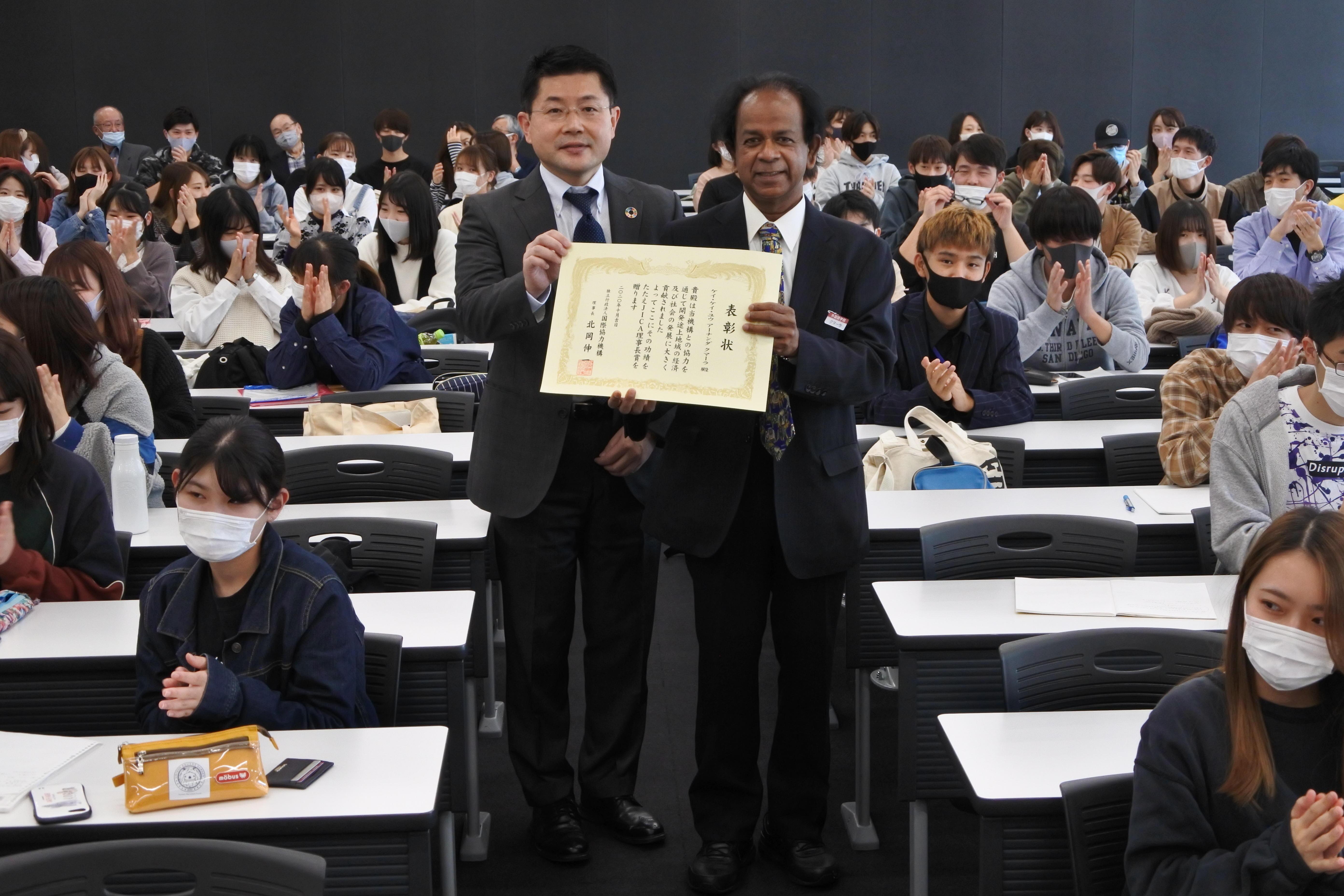 JICA理事長賞を受け、学生から拍手を浴びるアーナンダ・クマーラ教授(右)