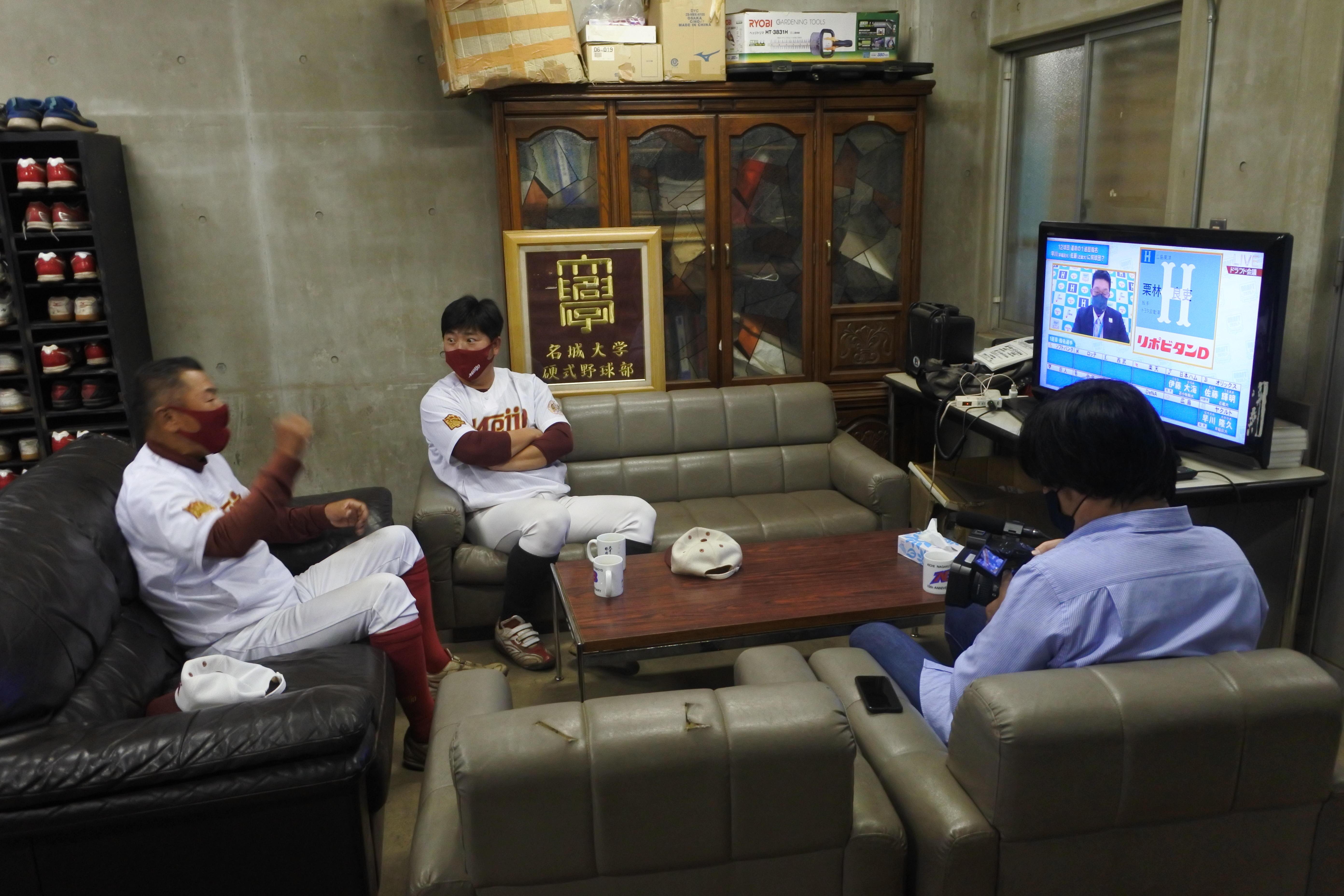 日進グラウンドで、テレビで広島の1位指名を見てガッツポーズする安江監督(左)