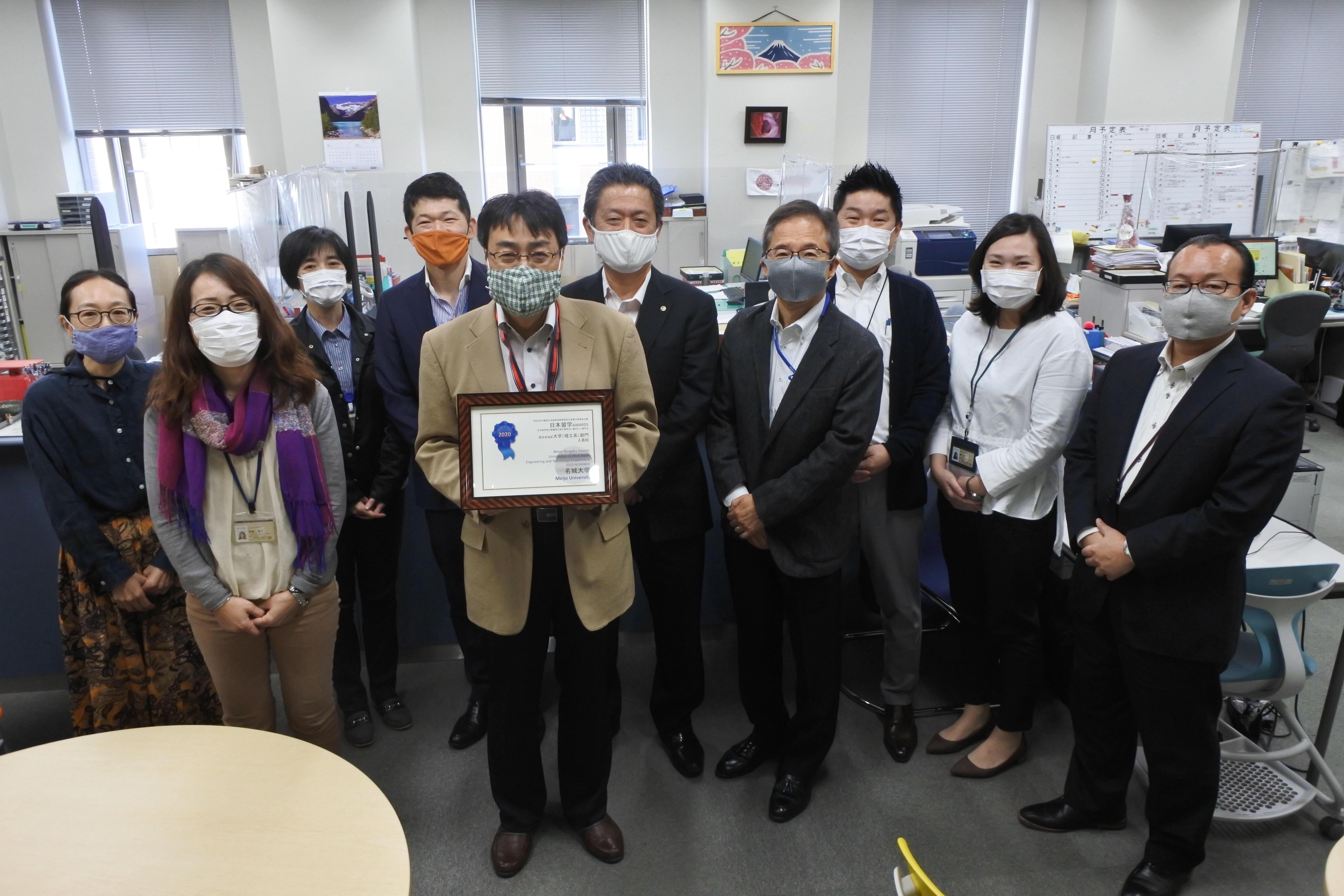 表彰状を手にする田中武憲国際化推進センター長と青山和順事務部長(中央)ら職員