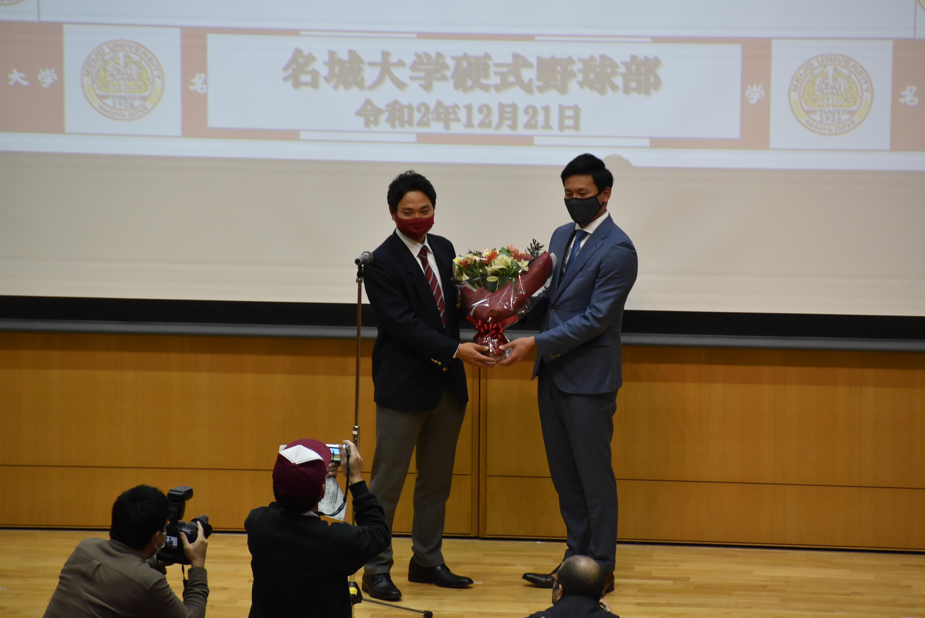 飯田隆志主将(左)から花束を受け取る栗林投手