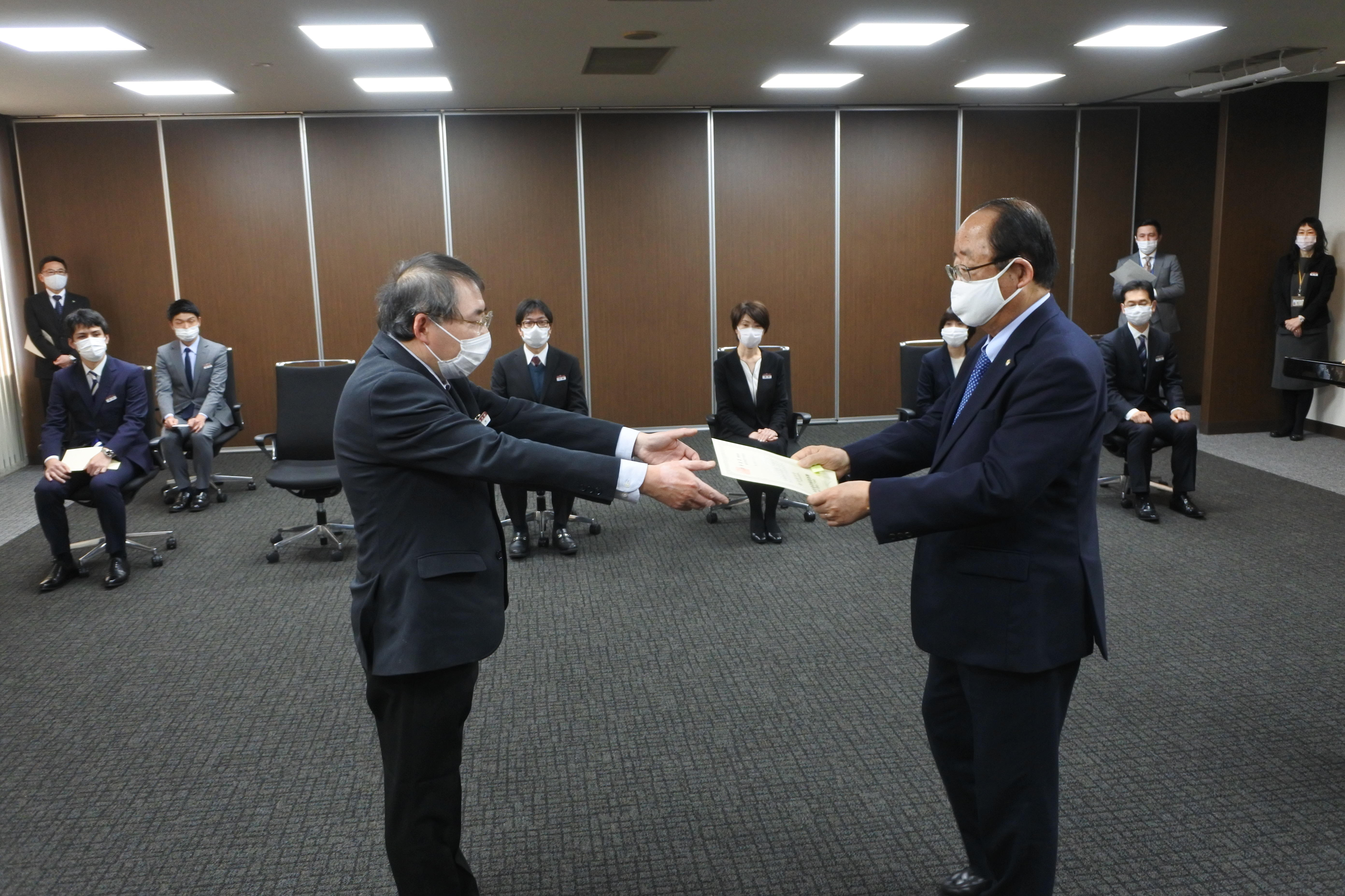 立花貞司理事長(手前右)から表彰状を受け取る鈴木厚司外国語学部事務室事務長