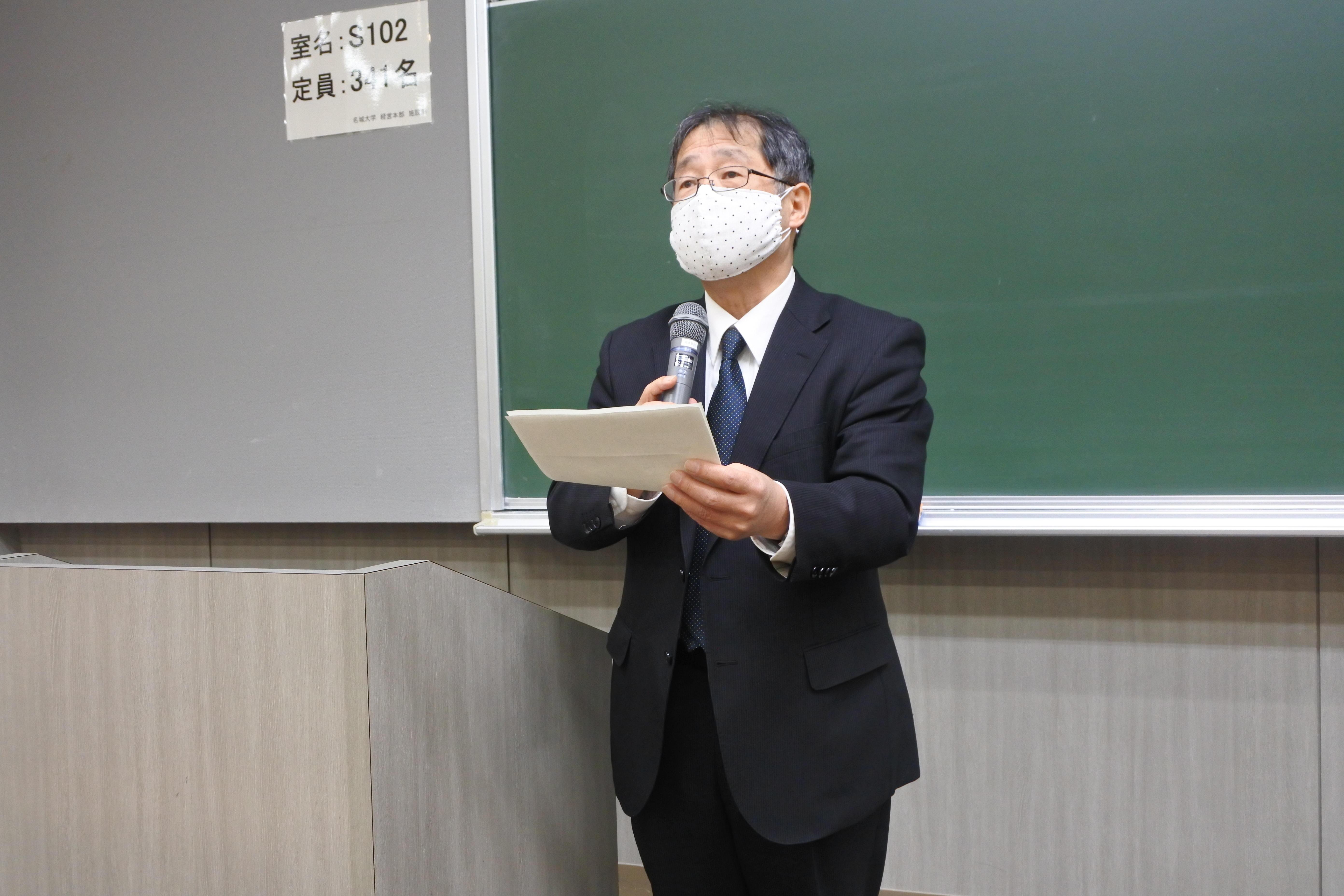 池上彰教授のメッセージを代読する運営委員長の大野栄治副学長