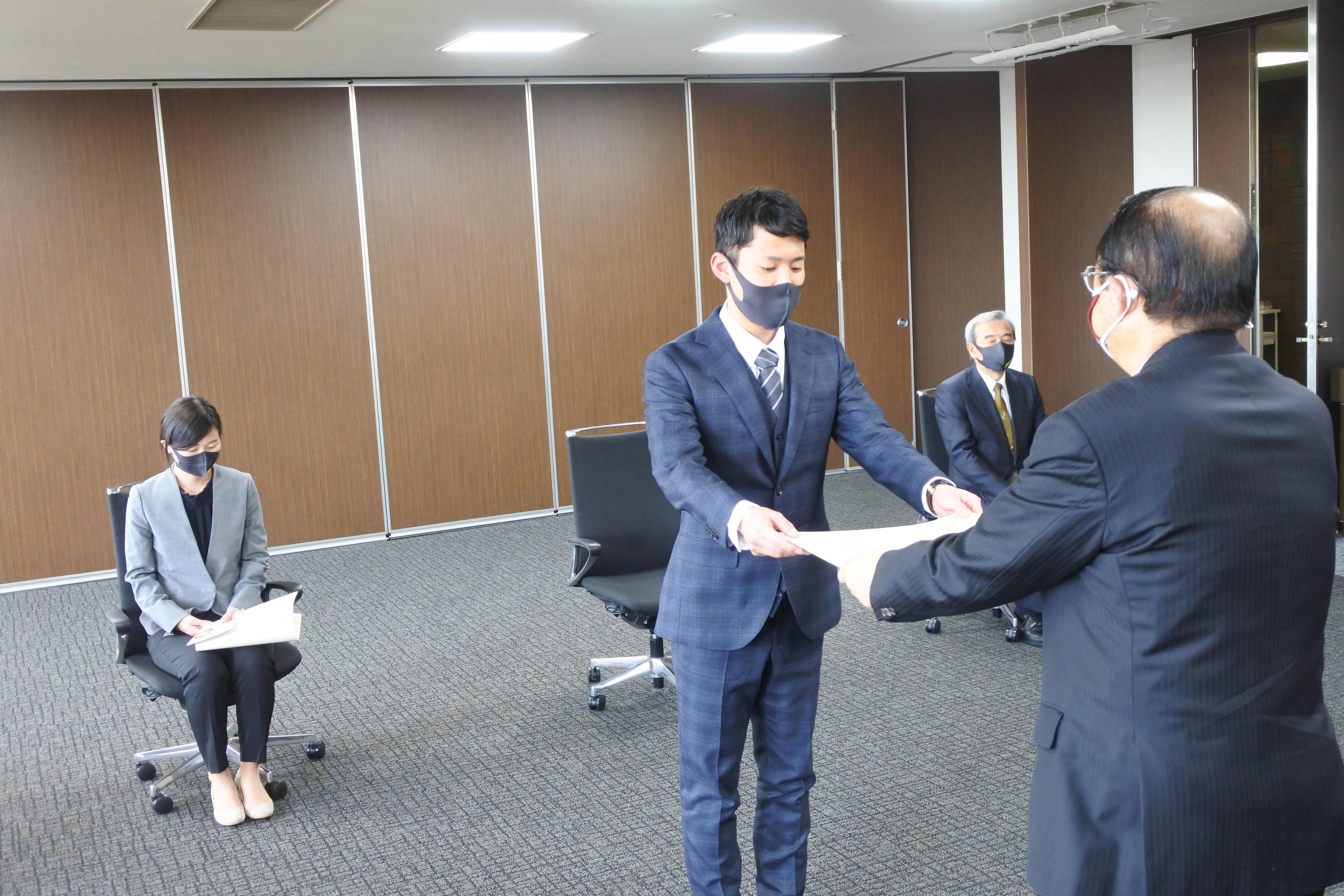 立花理事長から表彰状を受け取る玉城コーチ
